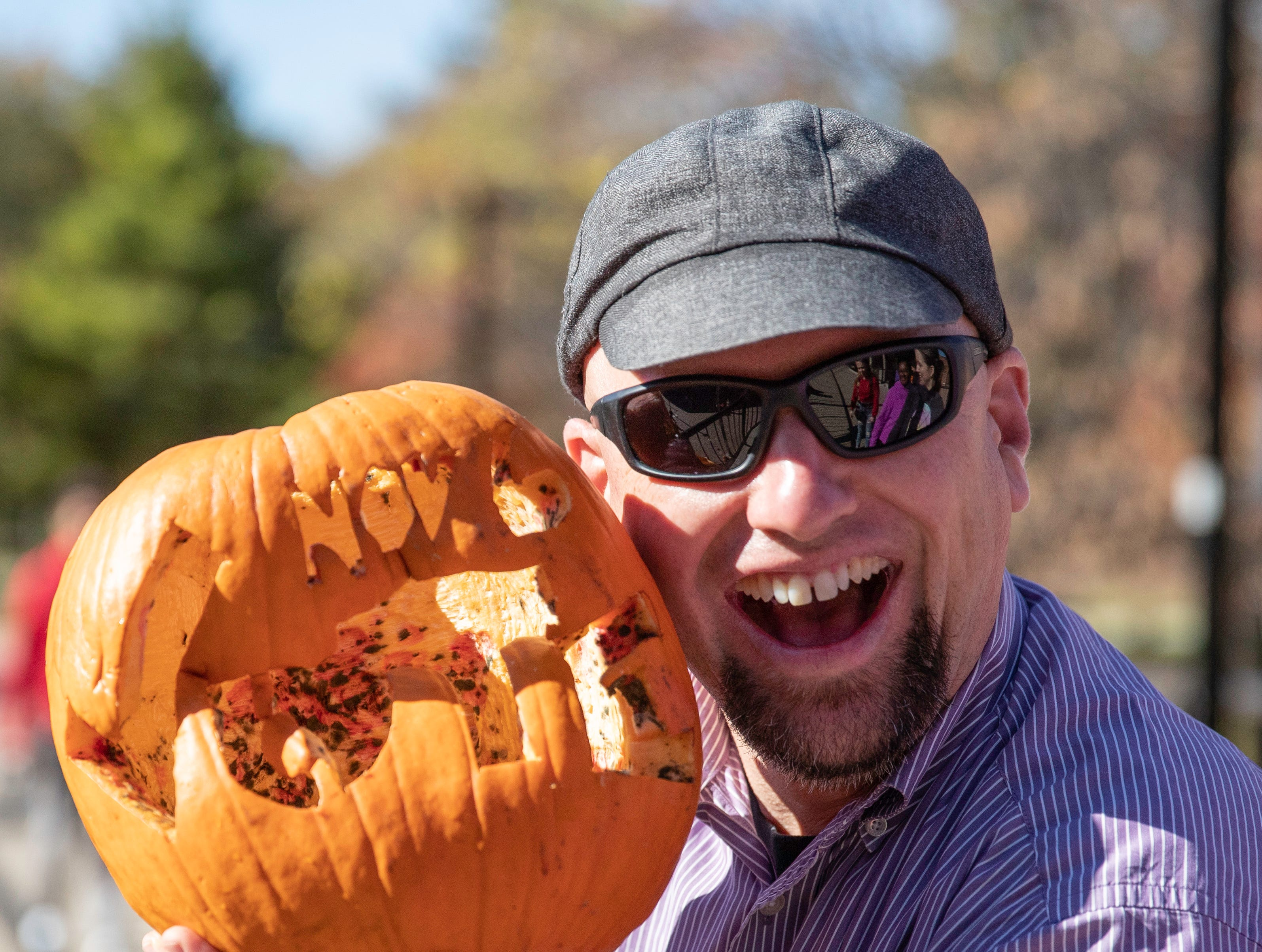 """Justin Mog, Ph.D., Assistant to the Provost for Sustainability Initiatives, holds up whats left of a """"Vote Nov. 6"""" pumpkin near the UofL Student Activities Center, Tuesday, Nov. 6, 2018 in Louisville Ky. """"This is quickly becoming one of my favorite events of the year! Not only does sustainability require that we compost, and vote, and relieve stress healthfully, but it also requires us to smash the old way of doing things and disrupt business as usual. That's what this event is all about."""" Mog said."""