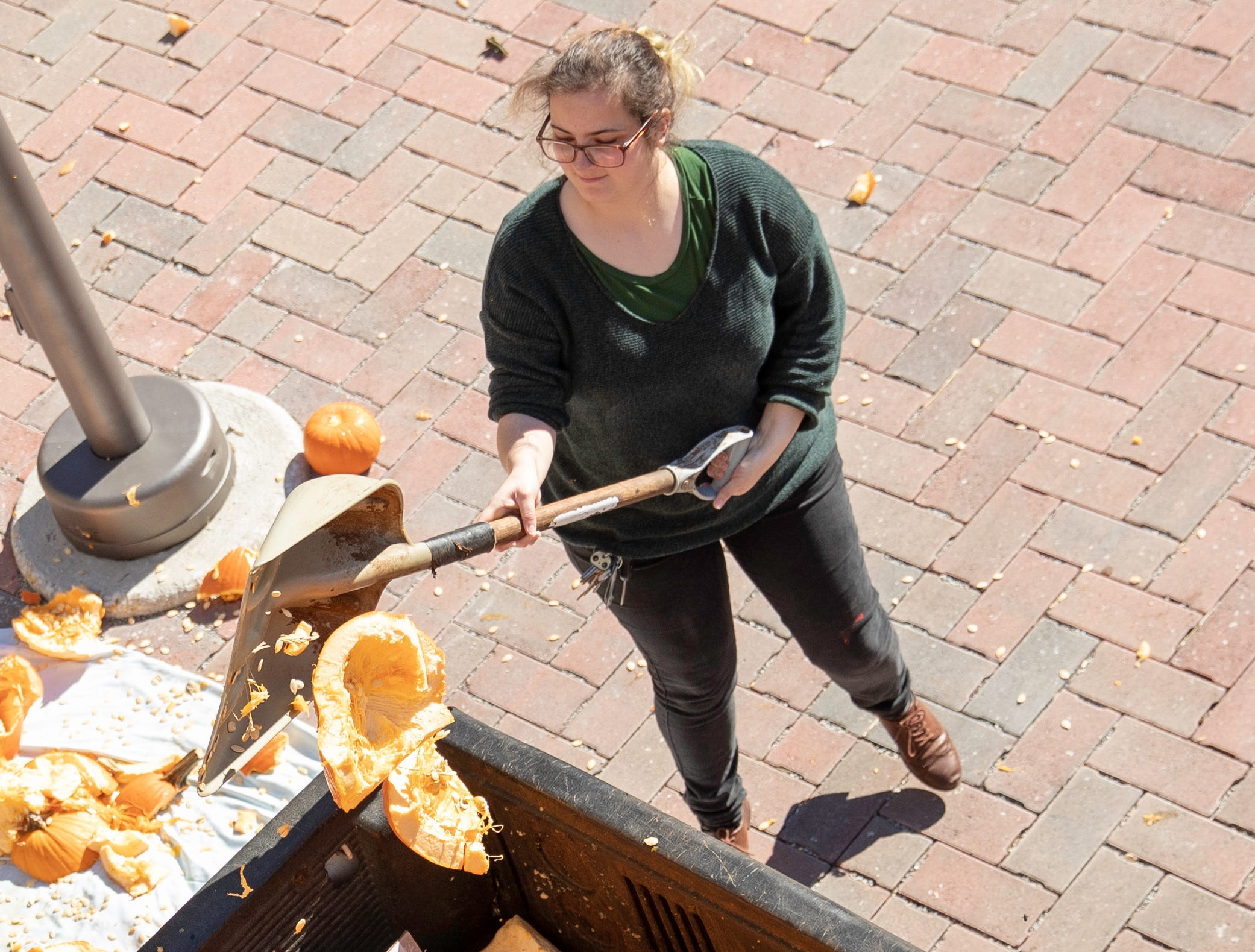 """Erin Kurtz cleans up smashed pumpkins during the second annual Pumpkin Smash event, Tuesday, Nov. 6, 2018 in Louisville Ky. Kurtz will be the first sustainability program graduate this December. """"I was supposed to be a senior when it came about and I just kind of changed everything to fit it in because it was something that I'm really passionate about."""" Kurtz said. """"We need to participate in the elections so we can have people that support our views and make change in relation to sustainability and sustaining our communities in the best way possible. We need to find the right people that can do that."""""""