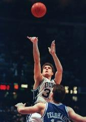 Duke's Christian Laettner shoots the game-winning basket in overtime over Kentucky's Deron Feldhaus to win the East Finals NCAA college basketball game, in Philadelphia. Duke beat Kentucky 104-103.