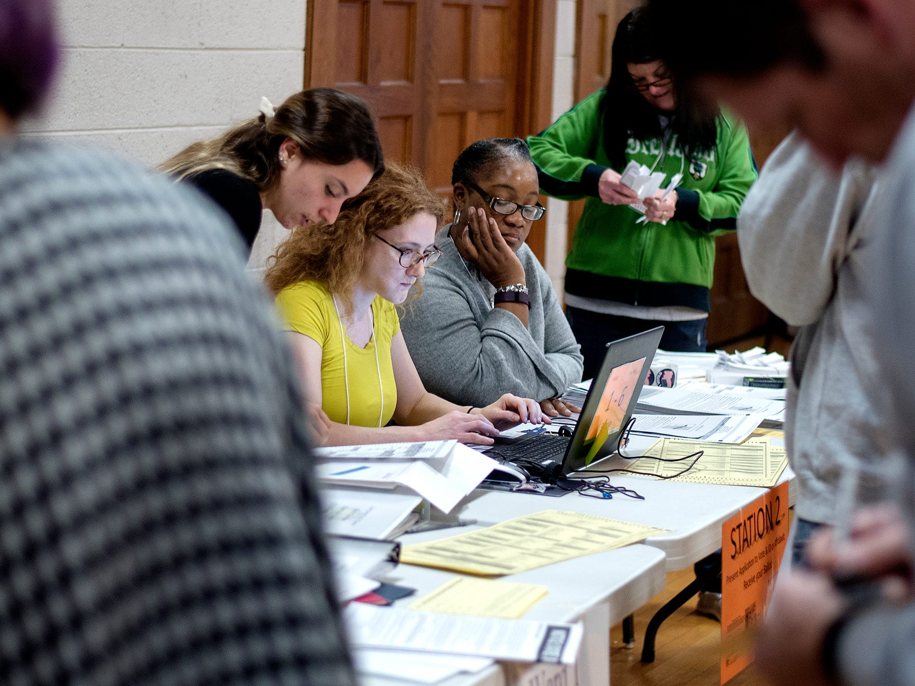 Election workers help voters register on Tuesday, Nov. 6, 2018, at Pilgrim Congregational United Church of Christ in Lansing.