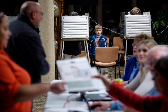 Eight-year-old Jacob Swanson, center, check out the activity as his father votes on Tuesday, Nov. 6, 2018, at the polling place inside Burcham Hills retirement community in East Lansing.