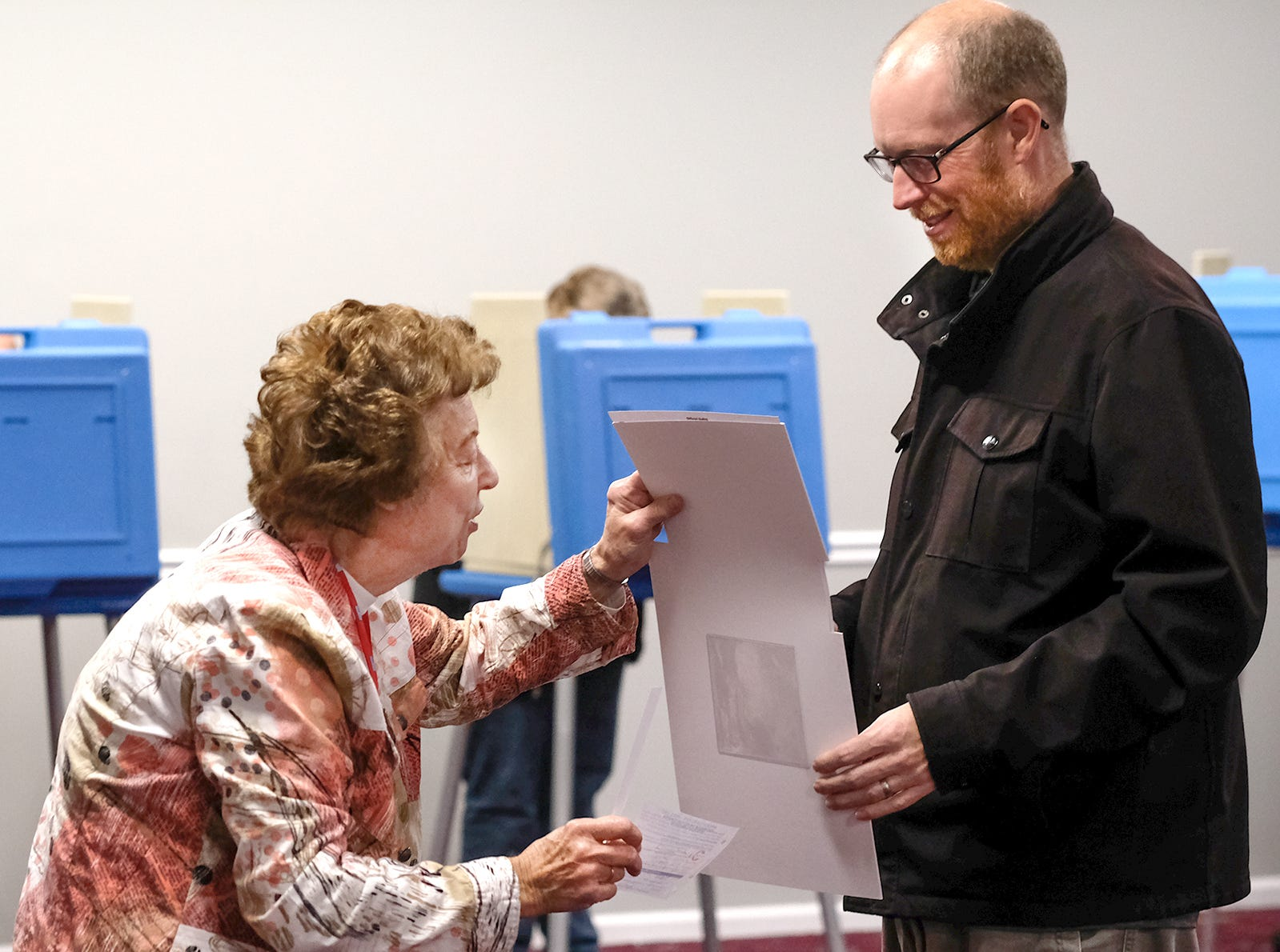 A polling station worker helps a voter as he gets ready to scan his ballot in Precinct 1 at Bingham Township Hall in St. Johns Tuesday, Nov. 6, 2018.