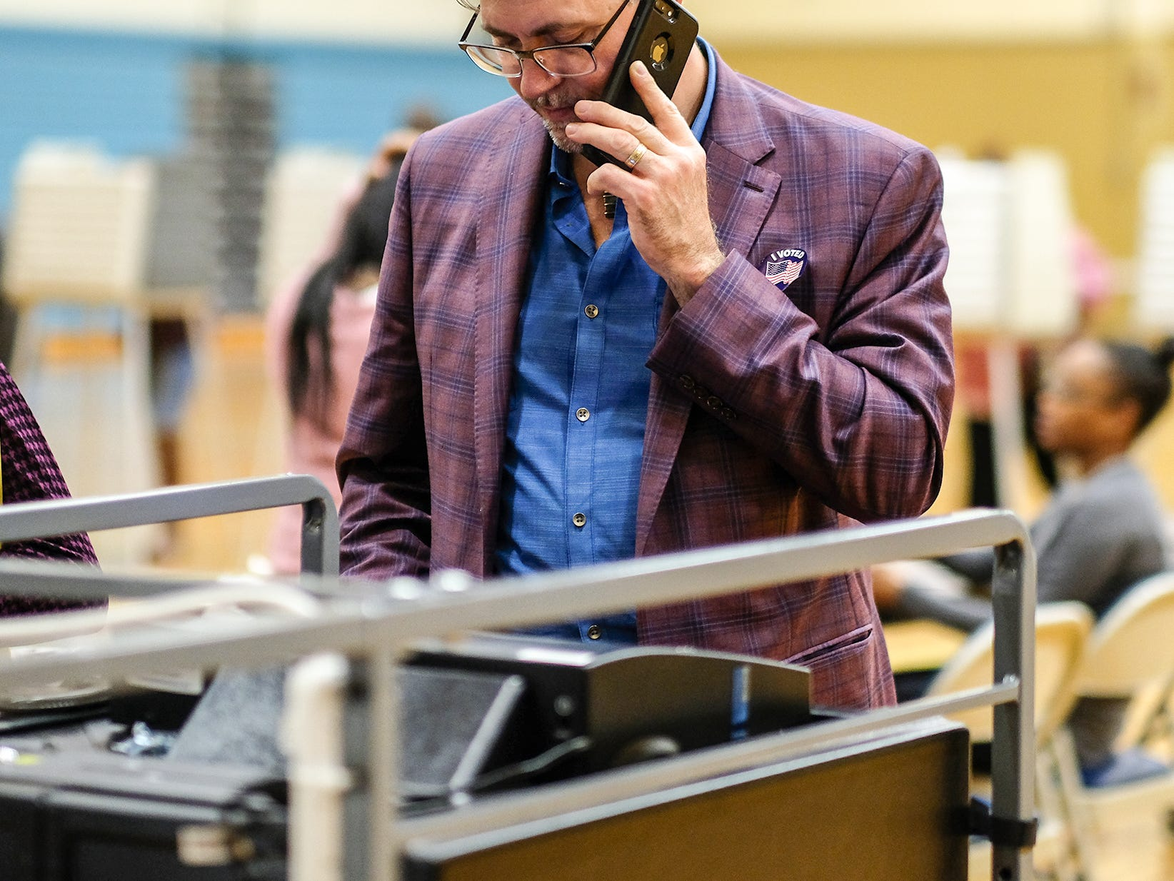 Lansing City Clerk Chris Swope is on the phone as he checks out a tabulator he ended up having to replace at the Alfreda Schmidt Southside Community Center polling station Tuesday, Nov. 6, 2018.