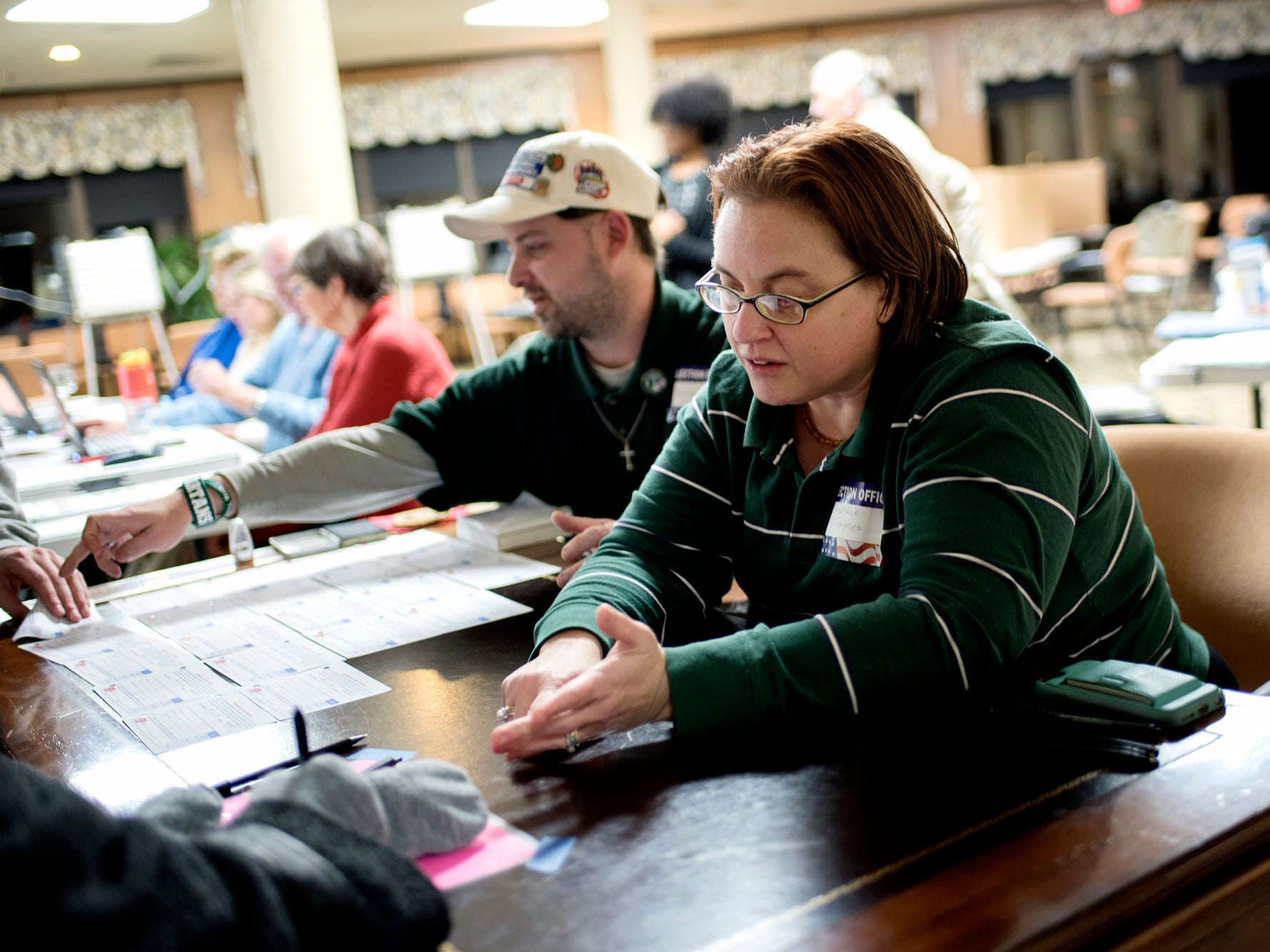 Poll worker Stephanie Grimes, right, and her husband Ben help voters get started on Tuesday, Nov. 6, 2018, at the polling place inside Burcham Hills retirement community in East Lansing.