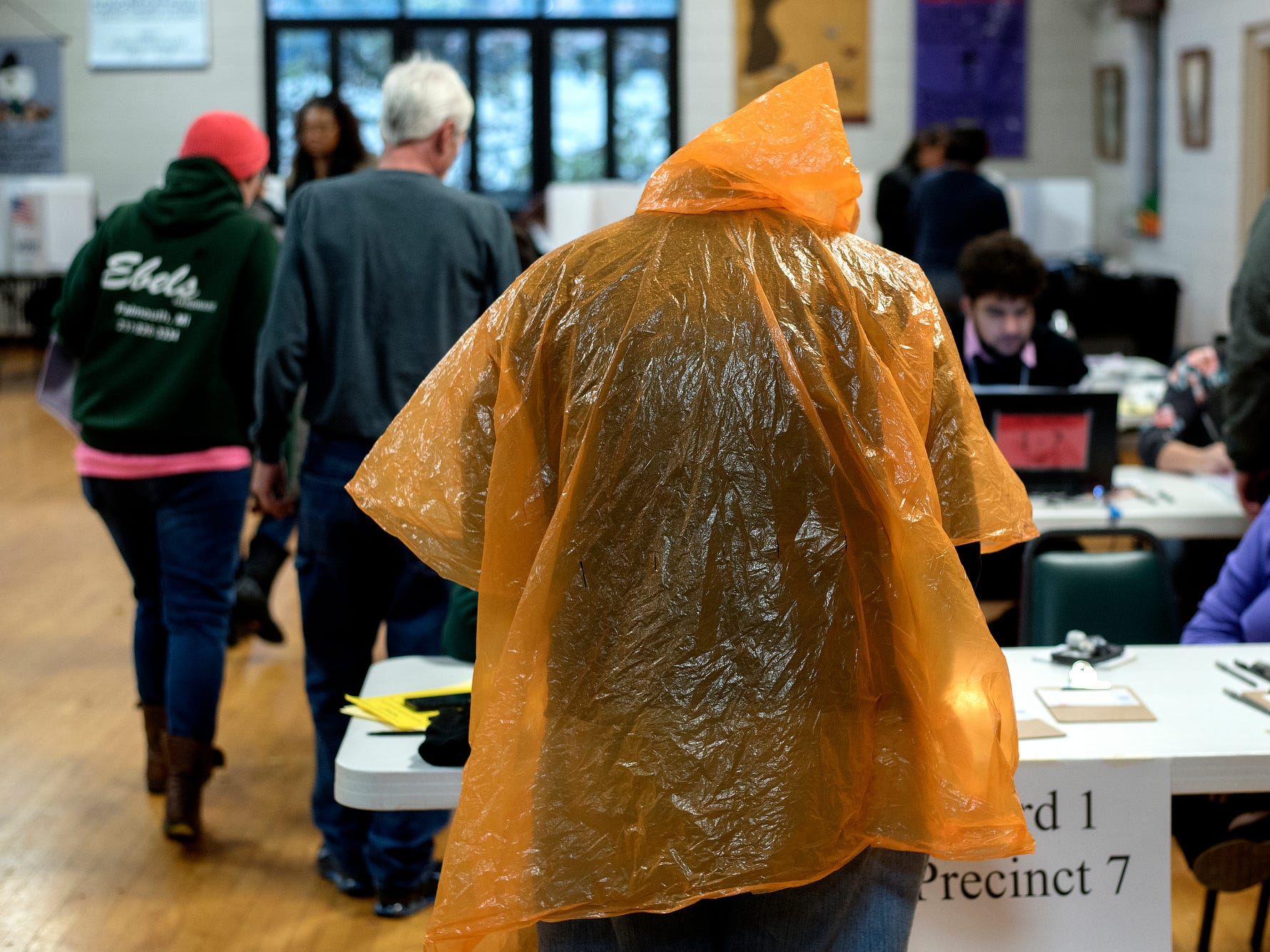 A voter wears a poncho after coming in from the rain to cast his ballot on Tuesday, Nov. 6, 2018, at Pilgrim Congregational United Church of Christ in Lansing.