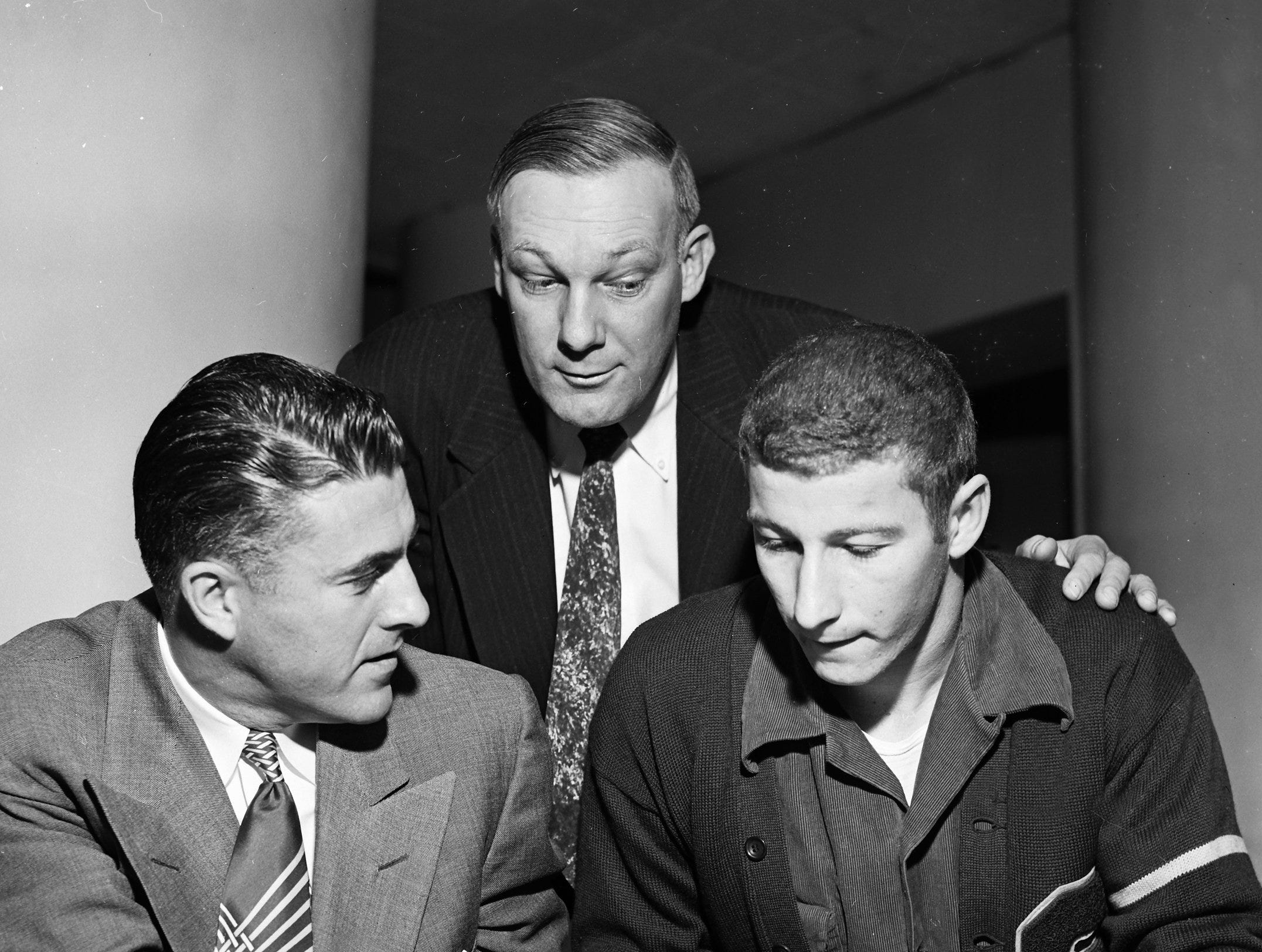Richard Moskovitz (Right), South Side halfback named as prep football player of the week by the Quarterback Club of Memphis the second week of November 1952, looks over grid action pictures in a magazine with his coach, Hick Ewing (Center) and Bob Swisher, one-time pro star and now a coach at Memphis Navy.  Moskovitz was honored for his play in South Side's 14-7 win over Tech the previous week.