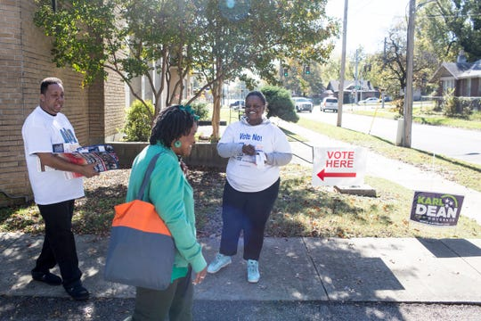 James Sidney, left, and Latasha Dickerson, right, campaign outside of a voting location inside of the Lewis Senior Center on Tuesday.