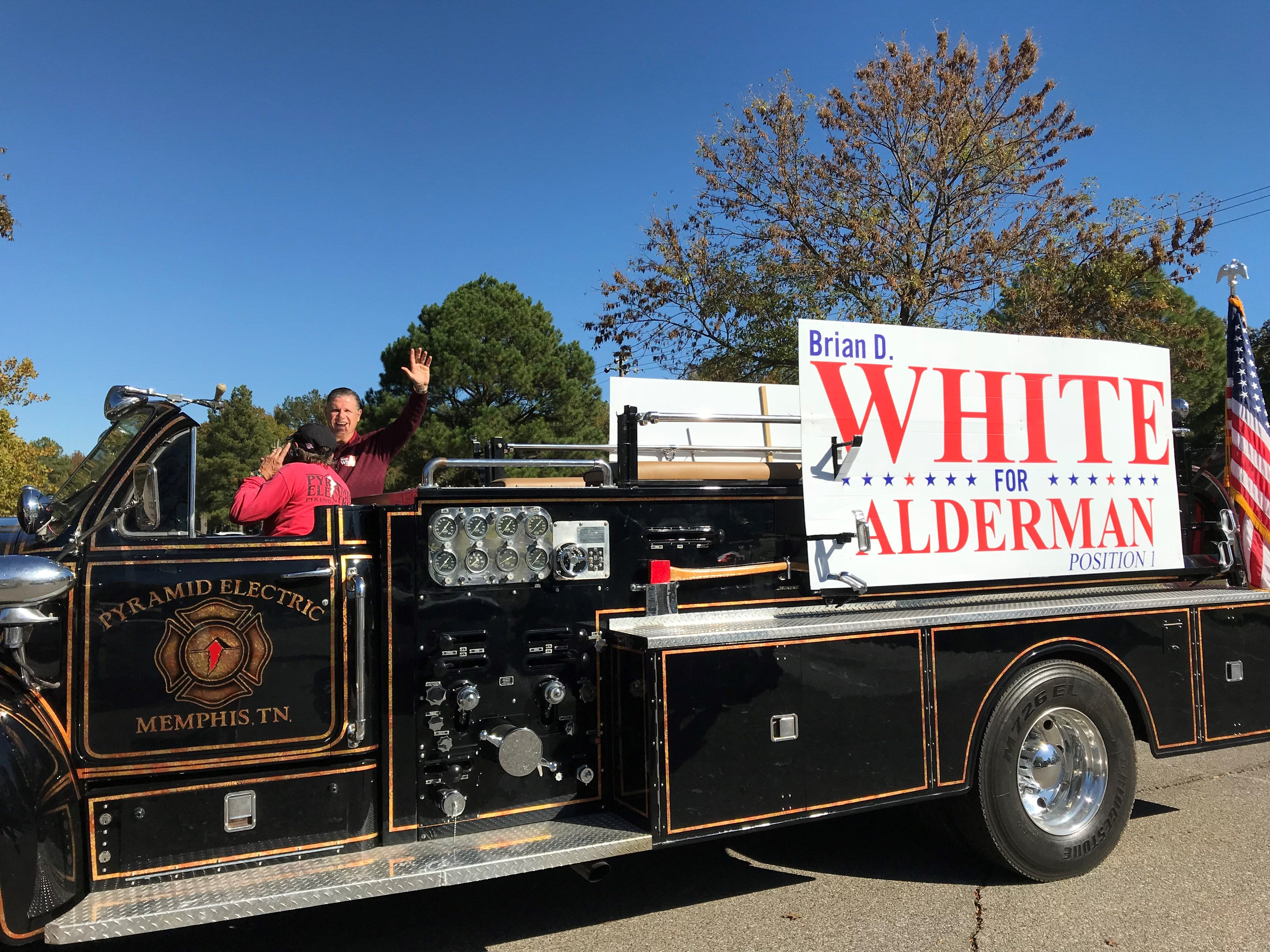 Germantown Alderman candidate Brian White waves from the top of a truck driven by a supporter outside Farmington Elementary School in Germantown.