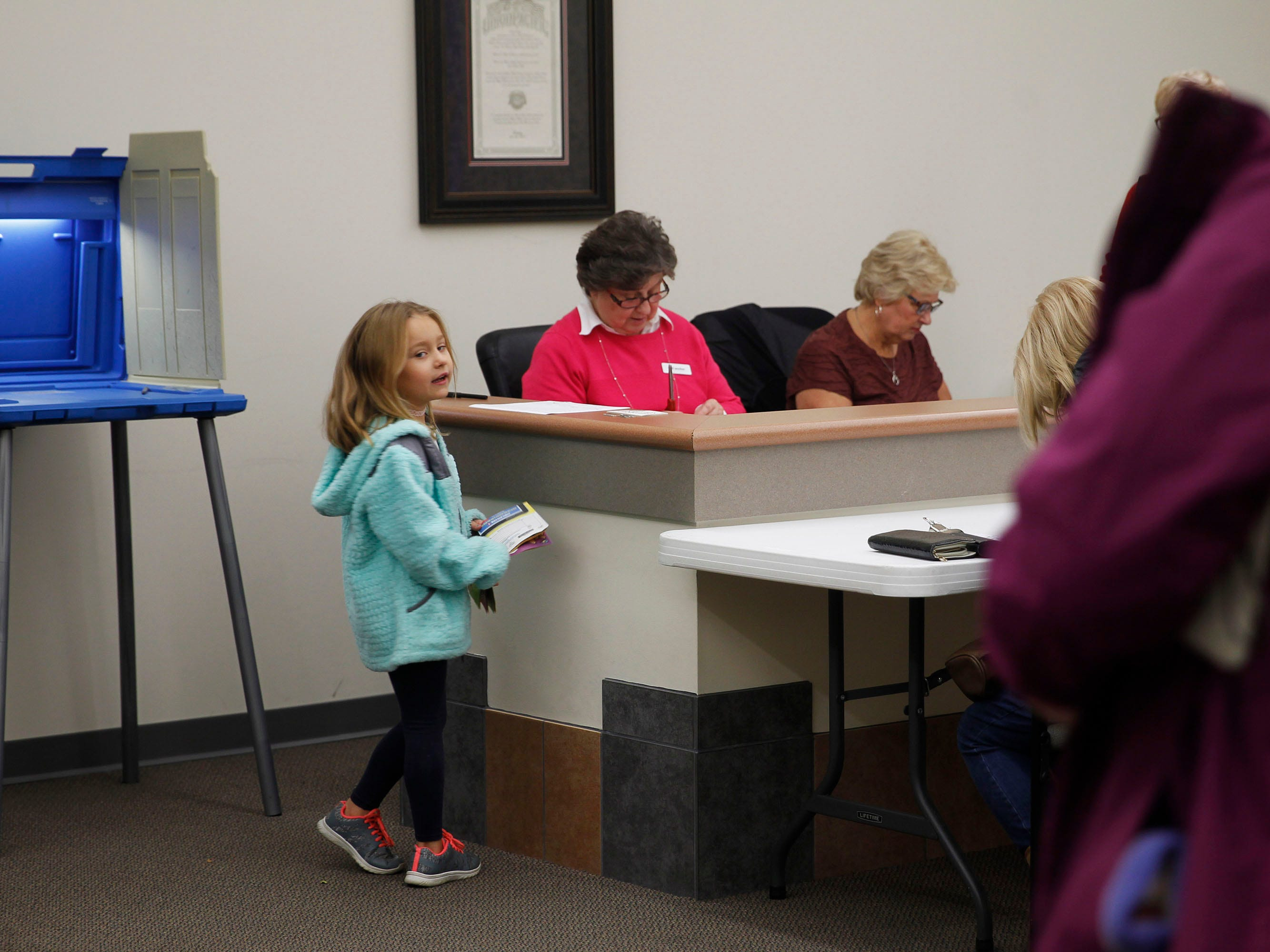 Audrey Ziegler, 6, is called by her mother, Jacquelyn, after saying hello to poll workers Kathy Eusslin (center) and Deputy Clerk Carolyn Jahnke at the village hall in Butler. Audrey was with her parents, who were among the early morning voters.