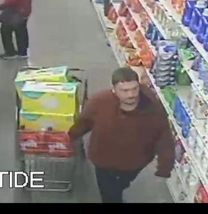 The alleged thief pulling a cart of merchandise inside of the Menomonee Falls Pick n Save.