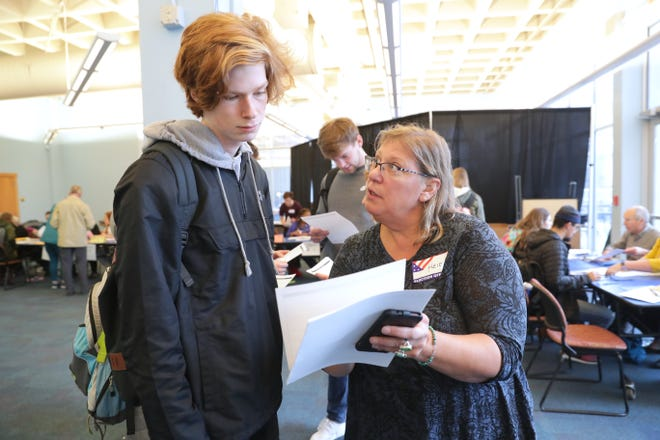 Poll worker Heidi Rose helps Kade Golden, an 18 year-old, register to vote. It was his first time voting.