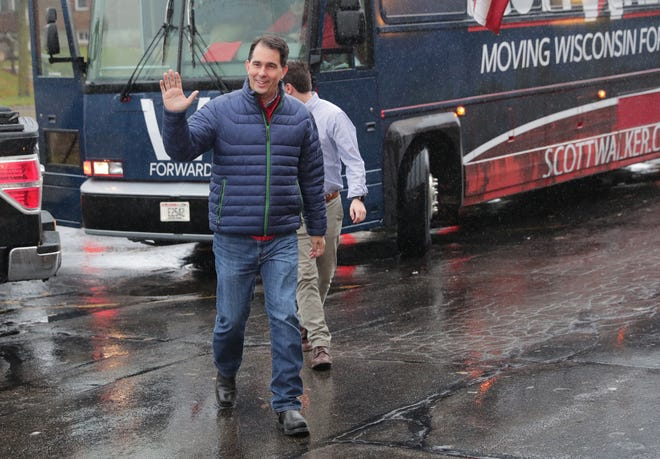 Scott Walker waves as he walks from his bus after last-minute campaigning at Johnny V's Classic Cafe on South 84th Street in Milwaukee in November.