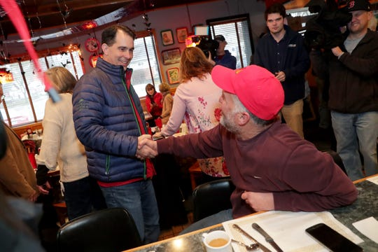 Gov. Scott Walker shakes hands with Paul Rachek of Antioch, Illinois, while doing some last-minute campaigning at Johnny V's Classic Cafe on South 84th Street in Milwaukee on Tuesday.