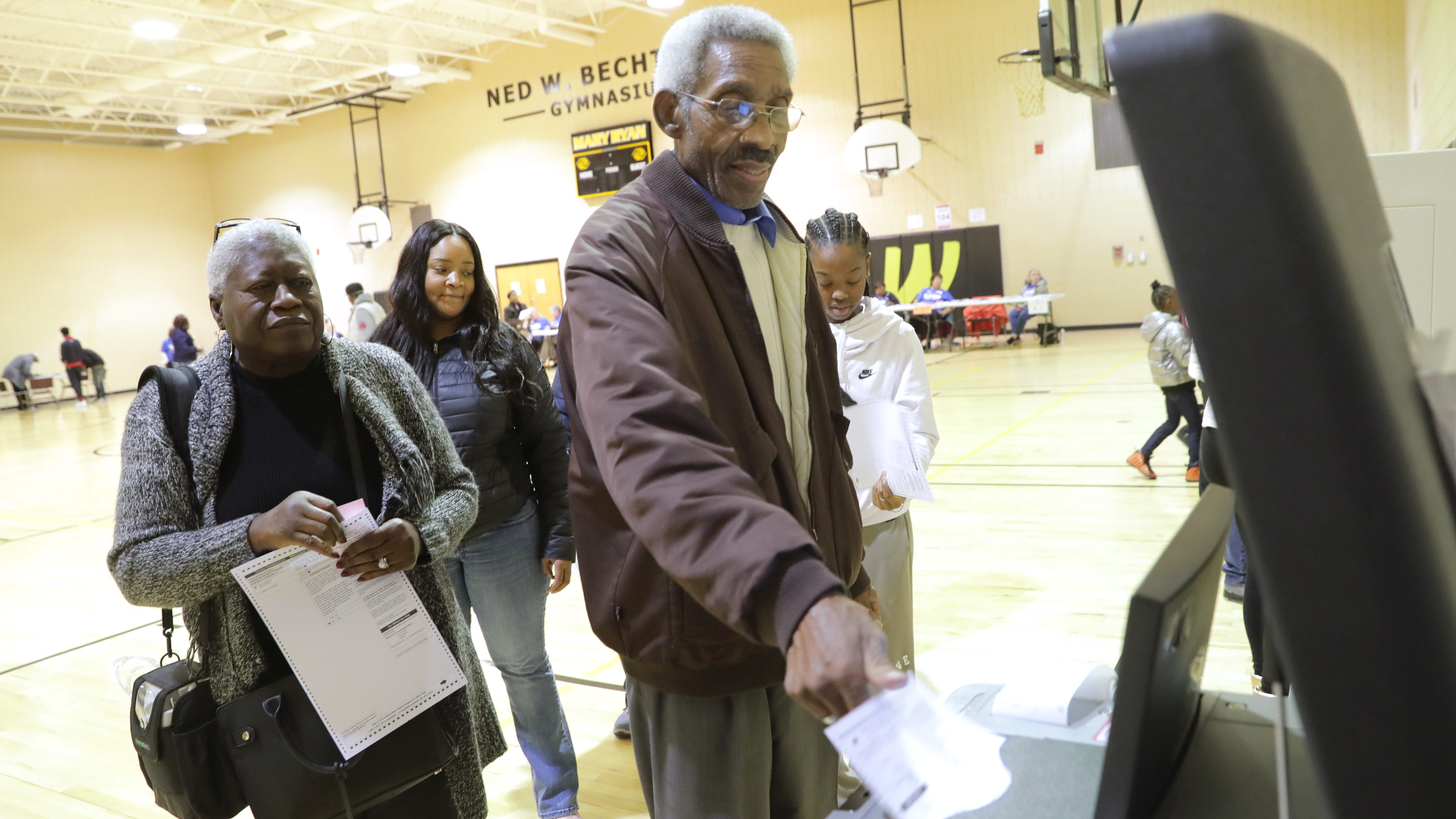 Charles McDowell of Milwaukee feeds his ballot after voting at the Boys and Girls Club in Sherman Park in Milwaukee.