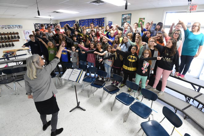 Pinkston Middle School Music teacher Sherry Mohler leads her students through a patriotic song Tuesday in preparation for a free concert Thursday at ASUMH to honor veterans.