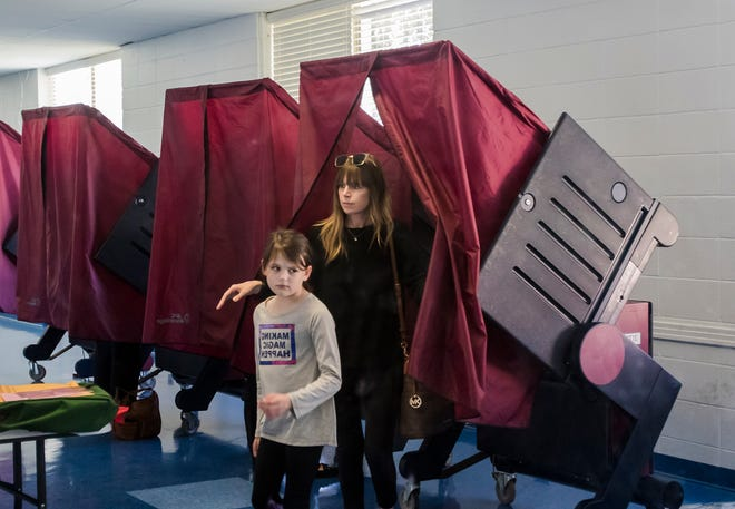 """Aubree Rogers, 8, and her mother Janna leave a voting booth at Saul Adler Community Center in Monroe, La. on Nov. 6's election day. """"She comes with me to learn how this works and to know that it's important to vote,"""" Janna said about her daughter joining her in the polling booth. """"The past few times she's come with me to vote. I think it's cool that she wants to come with."""""""