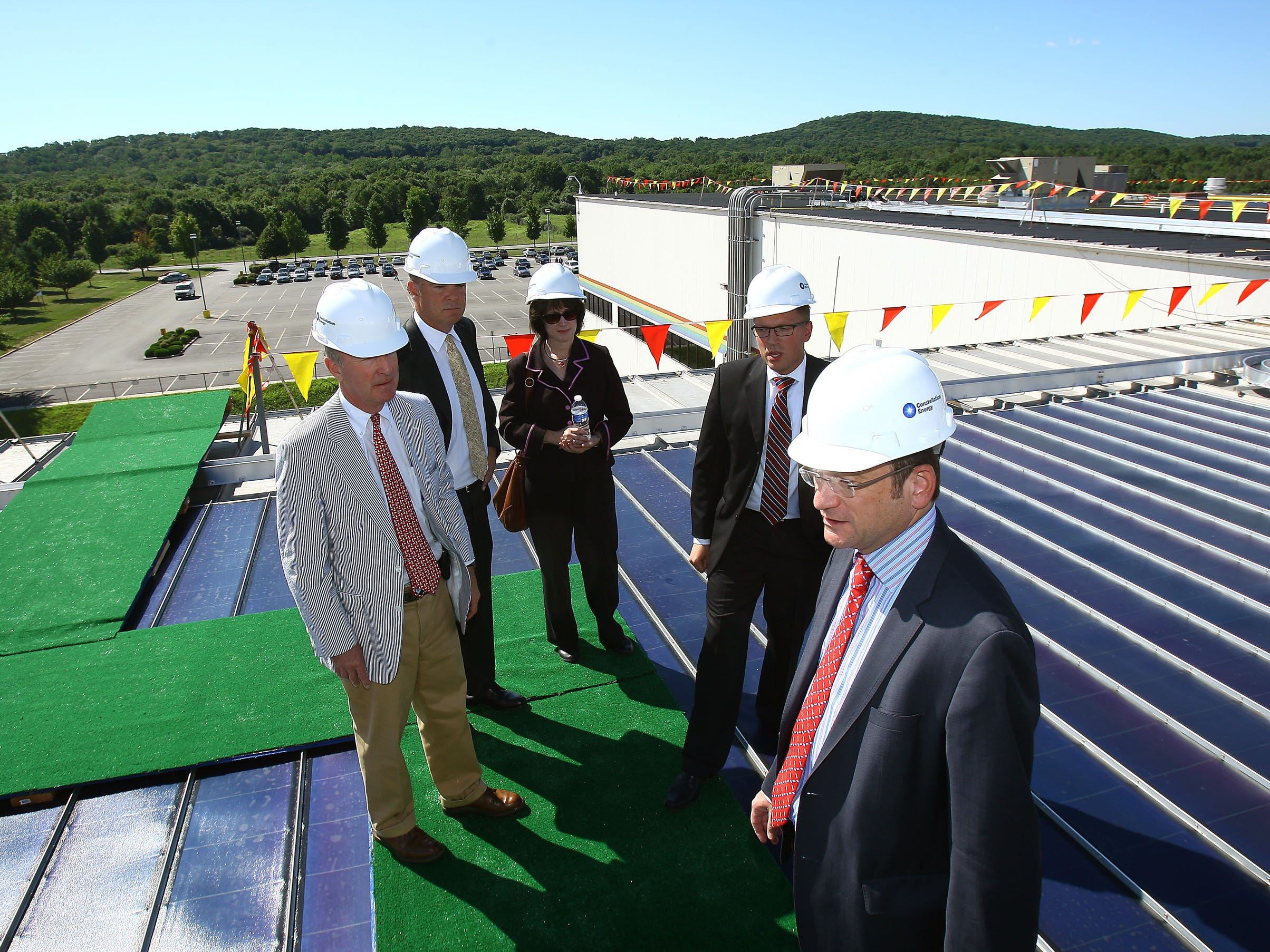 "Above: Rep. Rodney Frelinghuysen, (from left) state Department of Environmental Protection Commissioner Bob Martin; Chief Administrative Officer Deborah Derby; Kyle Bartz, director of energy management; and Jerry Storch, chairman and CEO of Toys"" R"" Us tour solar-panel lined roof in Flanders. Right: David Picot (left), a senior vice president at Toys ?R? Us, Storch and Martin unveil photo of the roof. bob karp/staff photographer"