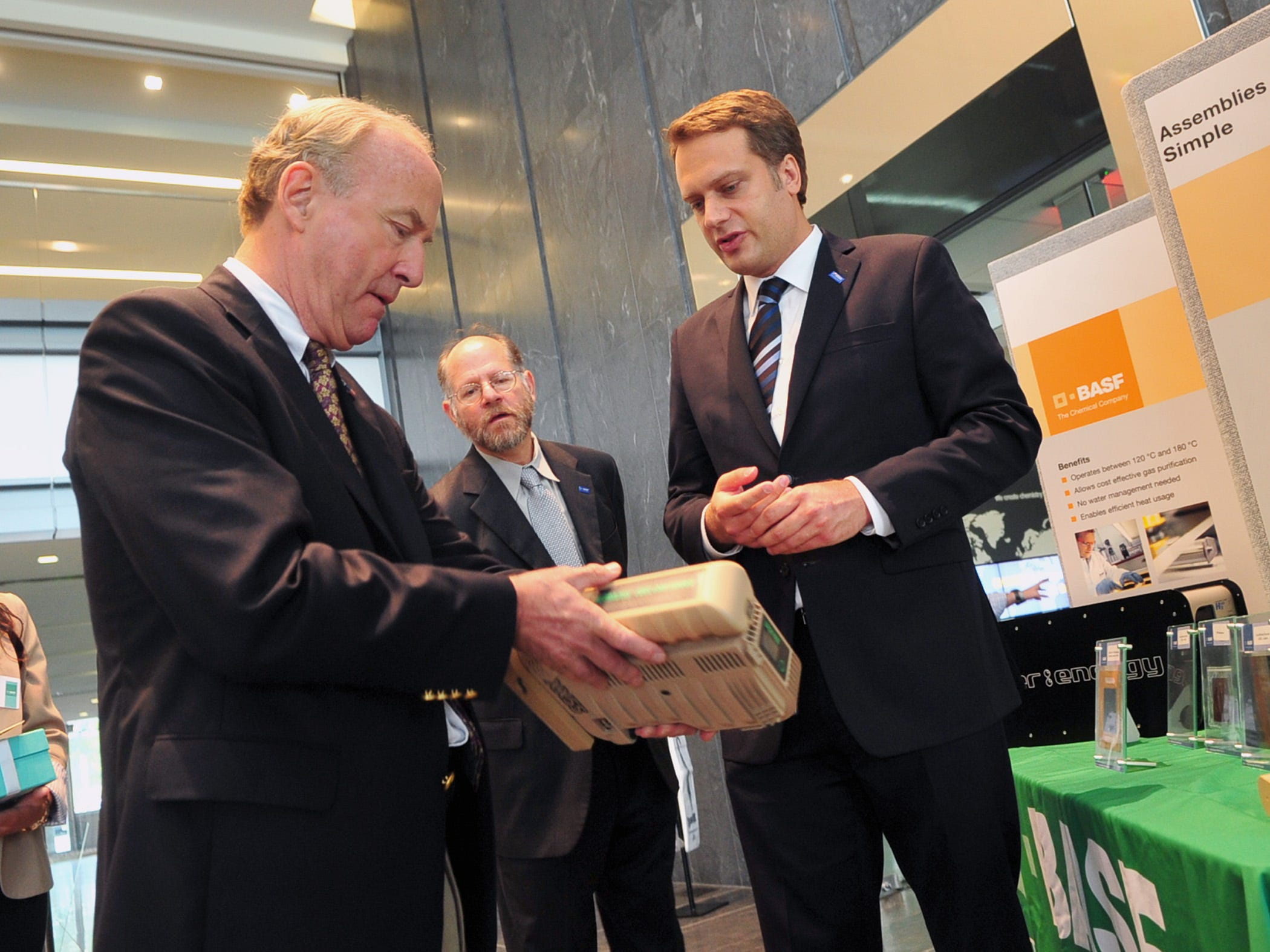 Rep. Rodney Frelinghuysen (left) looks over a portable fuel cell system used by the military with Moritz Ehrenstein (right), CEO of BASF, as Emory S. DeCastro, a BASF scientist and vice president of business management, looks on at BASF headquarters.  KAREN MANCINELLI/SPECIAL TO THE DAILY RECORD