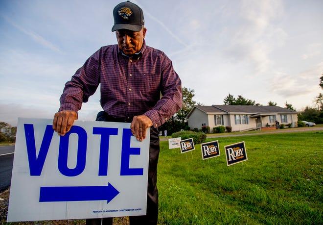 Snowdoun Women's Club voting place greeter James Jackson puts out Vote signs as the polls prepare to open in Snowdoun, Ala., on Tuesday November 6, 2018.