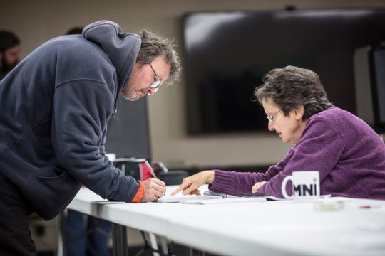 Voters at Precinct 39 inside the Farm Bureau Insurance Conference Room along Ind. 67 sign in with poll workers before casting their ballots on Tuesday. Polling stations across the areal reported a very steady flow of voters, unusually high for a mid-term election.