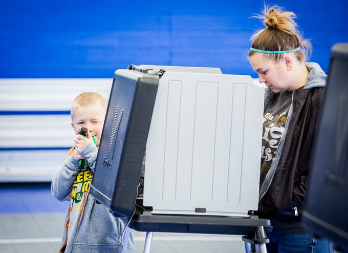 Lora Self casts her vote accompanied by her son, Jake, at the Muncie Boys and Girls Club Tuesday.