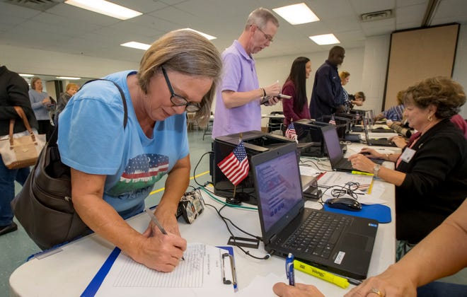 Gretchen Millspaugh signs paper work as she prepares to vote at SportsCom Tuesday morning in Murfreesboro.