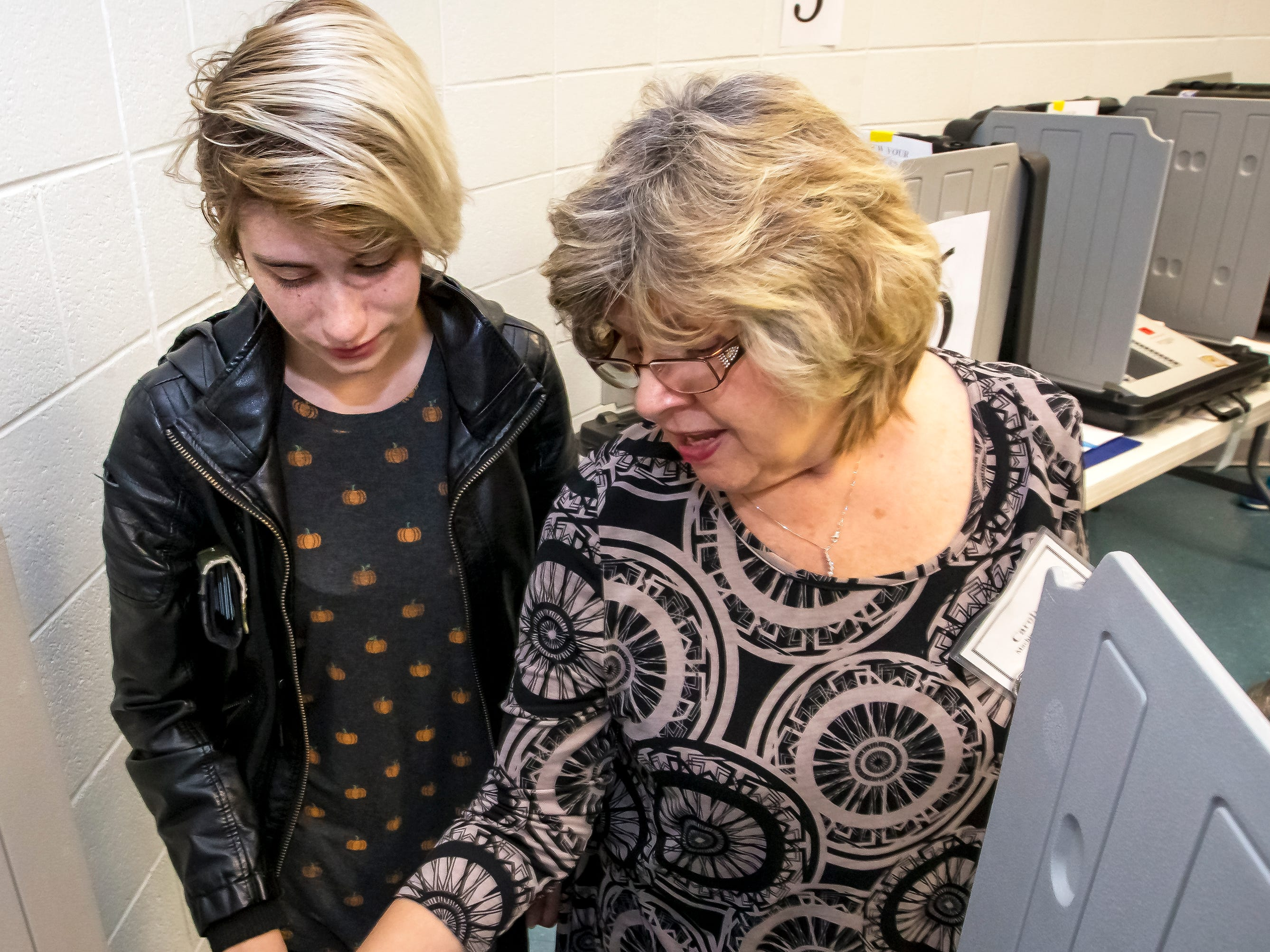 Carolyn McKnight, right, shows first time-voter, Alexis Yenney, left, how to use the voting machine at SportsCom Tuesday morning in Murfreesboro