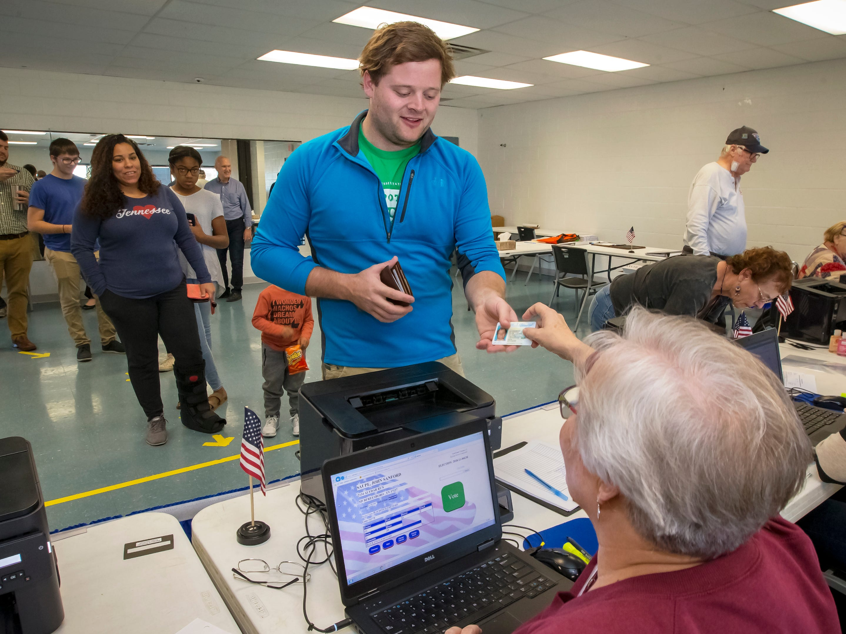 John Saupe shows at poll worker at SportsCom his ID as he prepares to vote Tuesday morning in Murfreesboro.