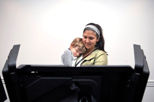 Nicole Dally of Franklin votes with her son, Hudson, 3, in her arms at the Westhaven Clubhouse polling location in Franklin, Tenn. on Tuesday, Nov. 6, 20-18.