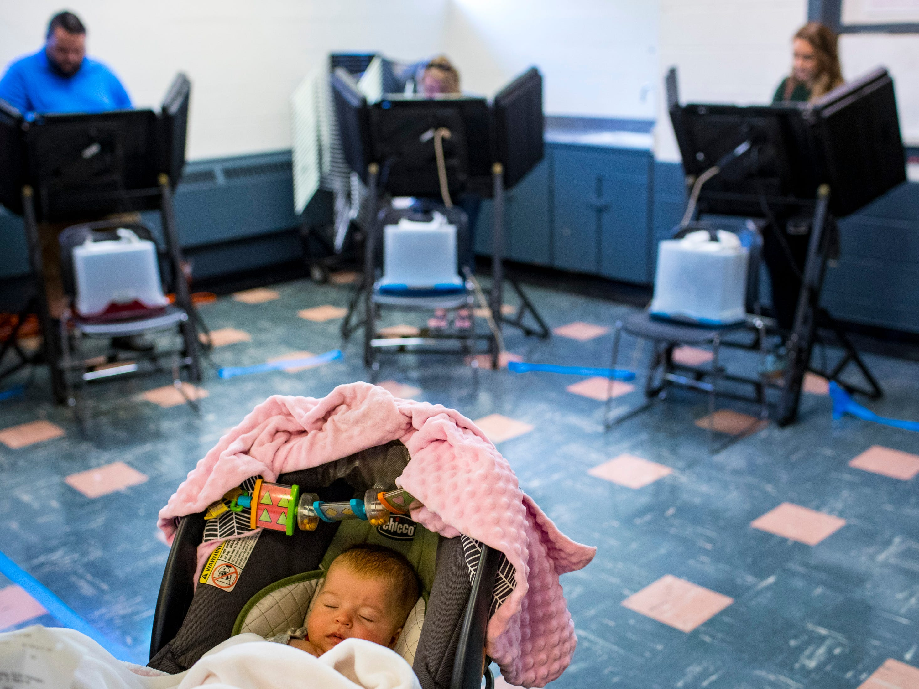 Mary Wells, 3 months, lies in a stroller while waiting in line at the Shelby Park Community Center polling place in Nashville on Tuesday, Nov. 6, 2018.