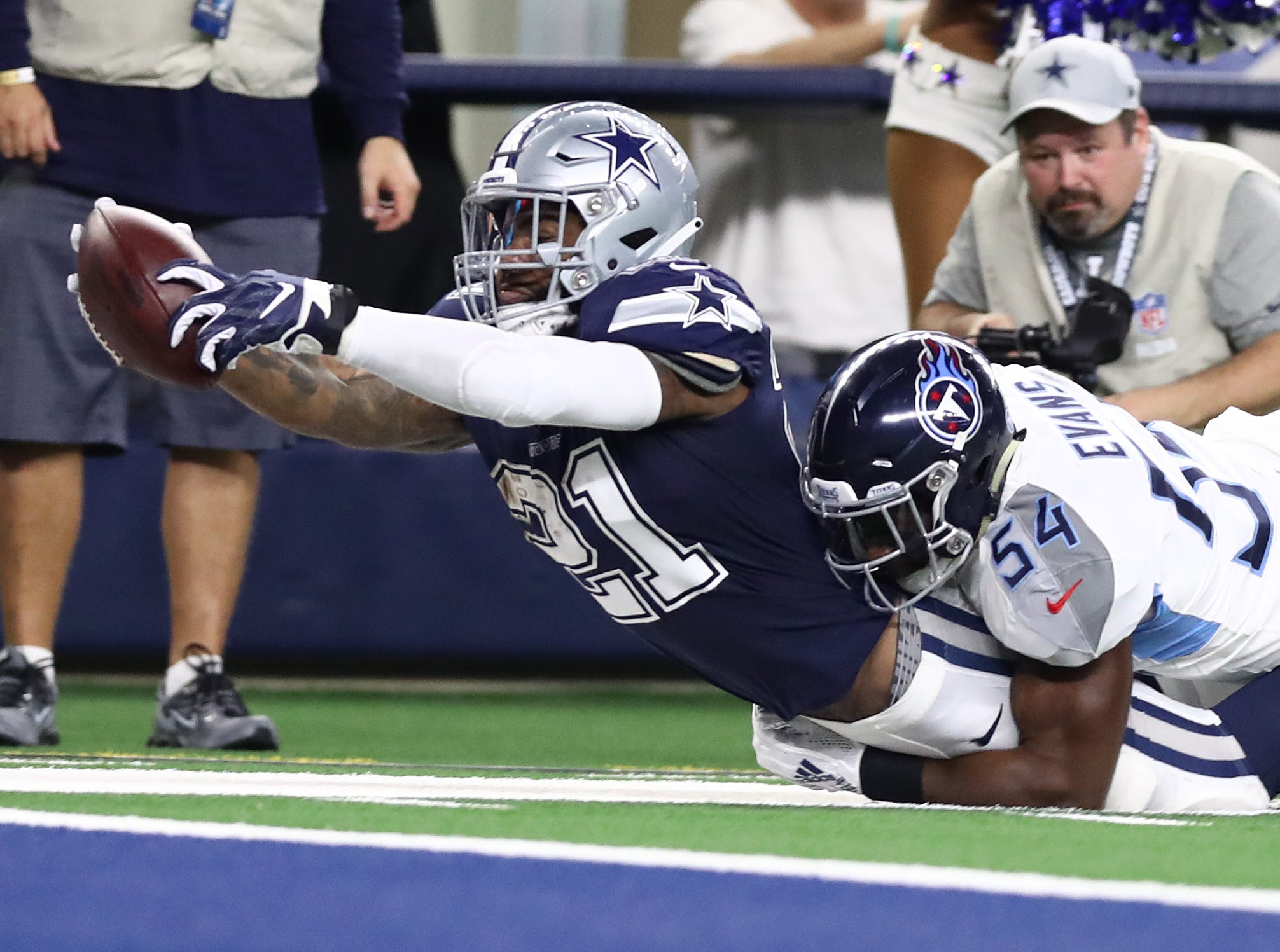 Nov 5, 2018; Arlington, TX, USA; Dallas Cowboys running back Ezekiel Elliott (21) dives for the goal line in the first quarter against Tennessee Titans linebacker Rashaan Evans (54) at AT&T Stadium.