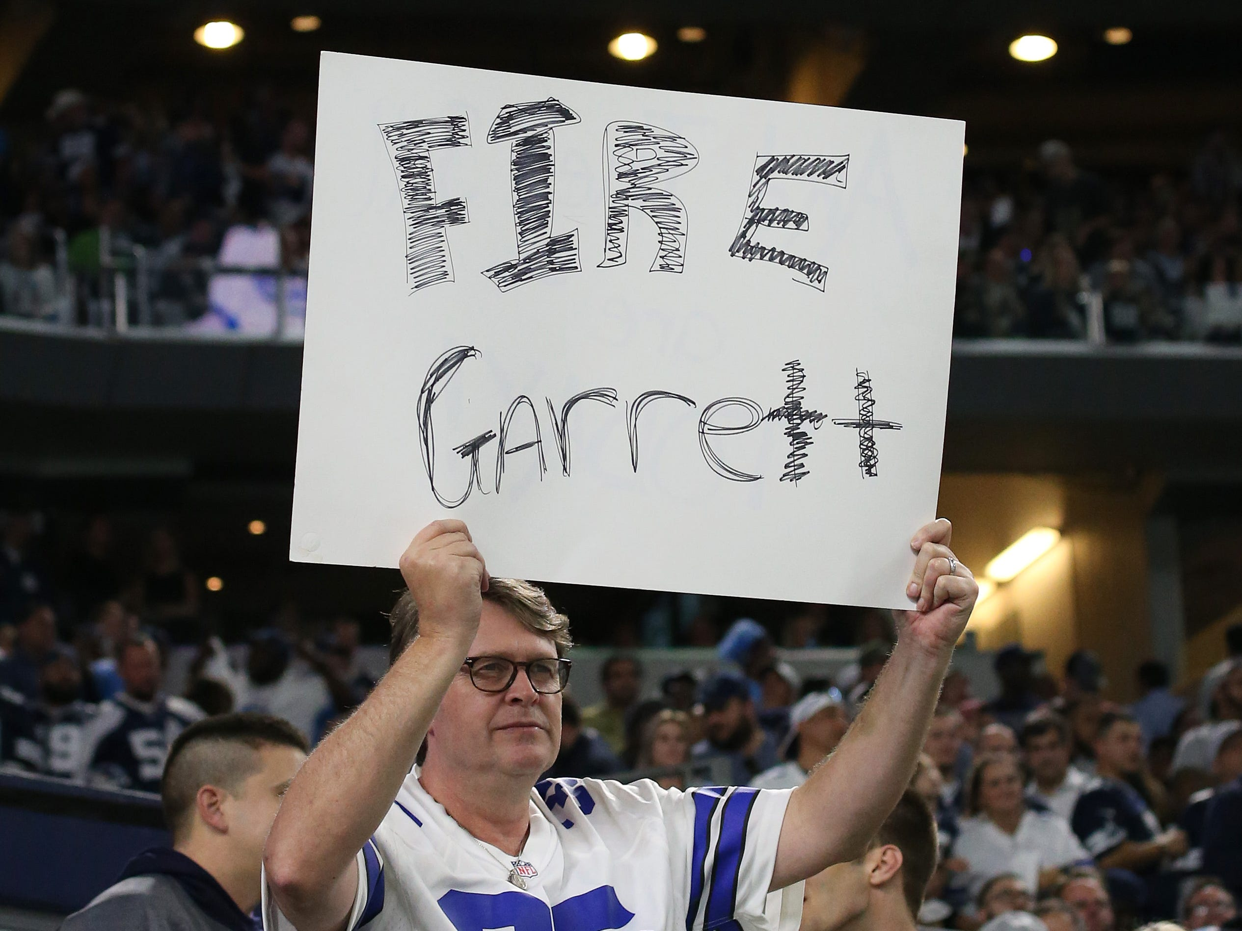 Nov 5, 2018; Arlington, TX, USA; Dallas Cowboys fan holds up a sign to fire head coach Jason Garrett during the fourth quarter against the Tennessee Titans at AT&T Stadium.