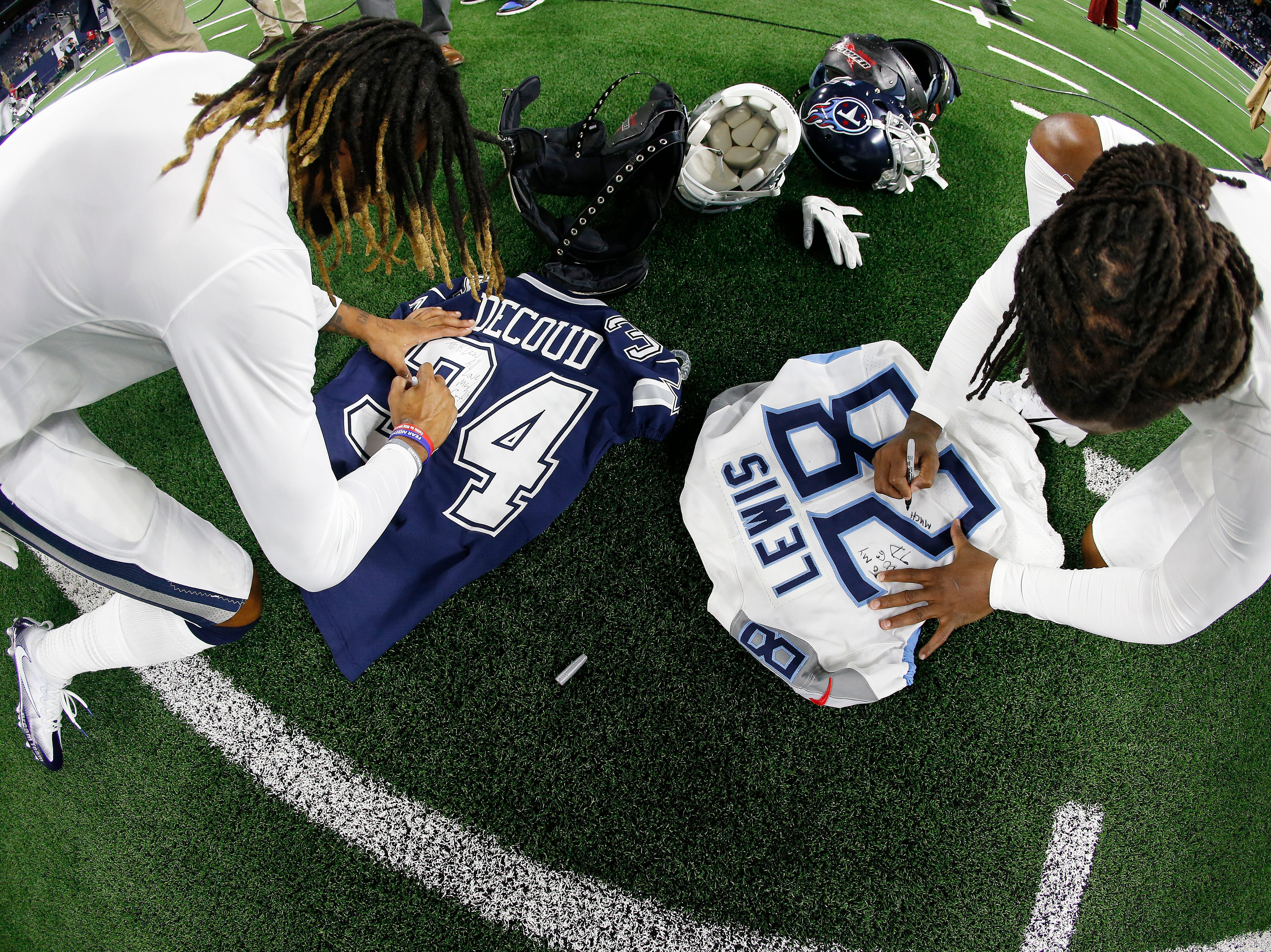 Tennessee Titans strong safety Kendrick Lewis (28) signs his jersey as Dallas Cowboys Treston Decoud does the same after an NFL football game, Monday, Nov. 5, 2018, in Arlington, Texas. The Tennessee Titans won 28-14.