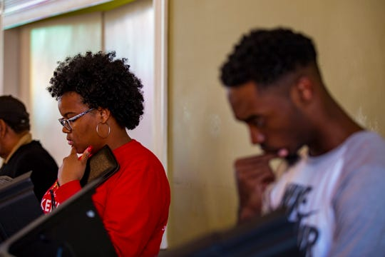 Desmond Parker, left, and Simeon Hall look over their ballots while voting at the Cathedral of Praise polling place in Nashville on Nov. 6, 2018.