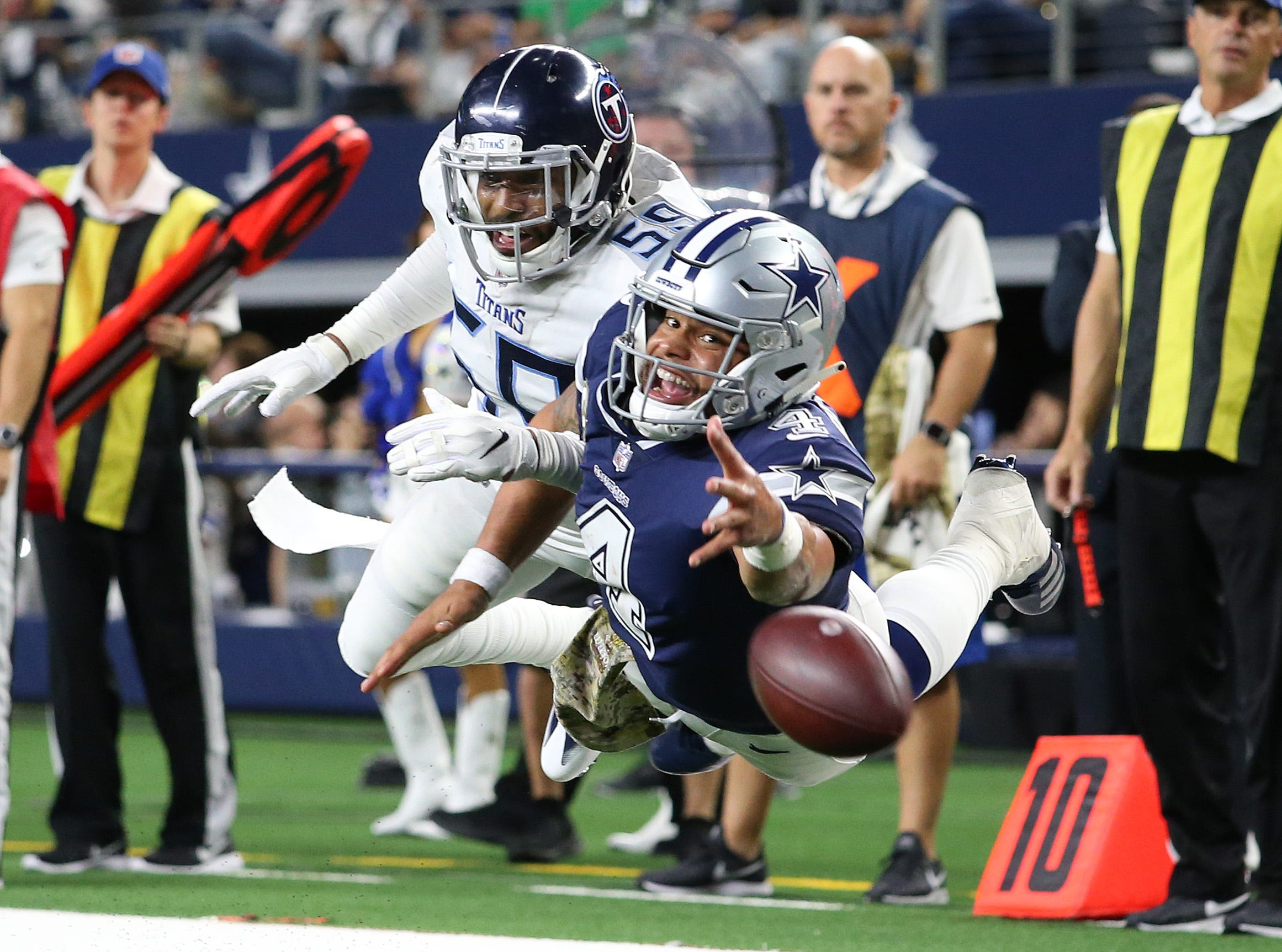 Dallas Cowboys quarterback Dak Prescott (4) dives for a pass in the fourth quarter against Tennessee Titans linebacker Wesley Woodyard (59) at AT&T Stadium. Mandatory Credit: Matthew Emmons-USA TODAY Sports