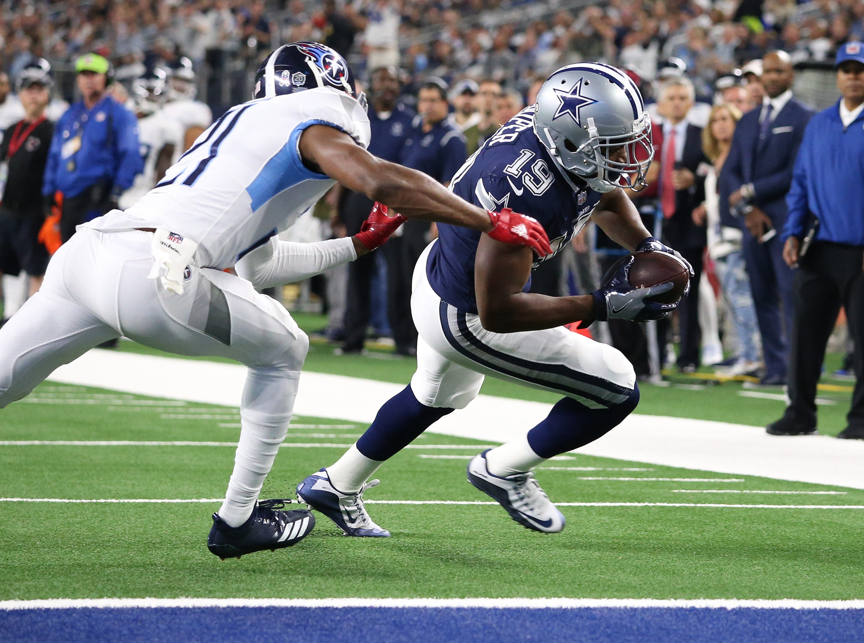 Nov 5, 2018; Arlington, TX, USA; Dallas Cowboys receiver Amari Cooper (19) runs after a reception for a first quarter touchdown against Tennessee Titans cornerback Malcolm Butler (21) at AT&T Stadium.