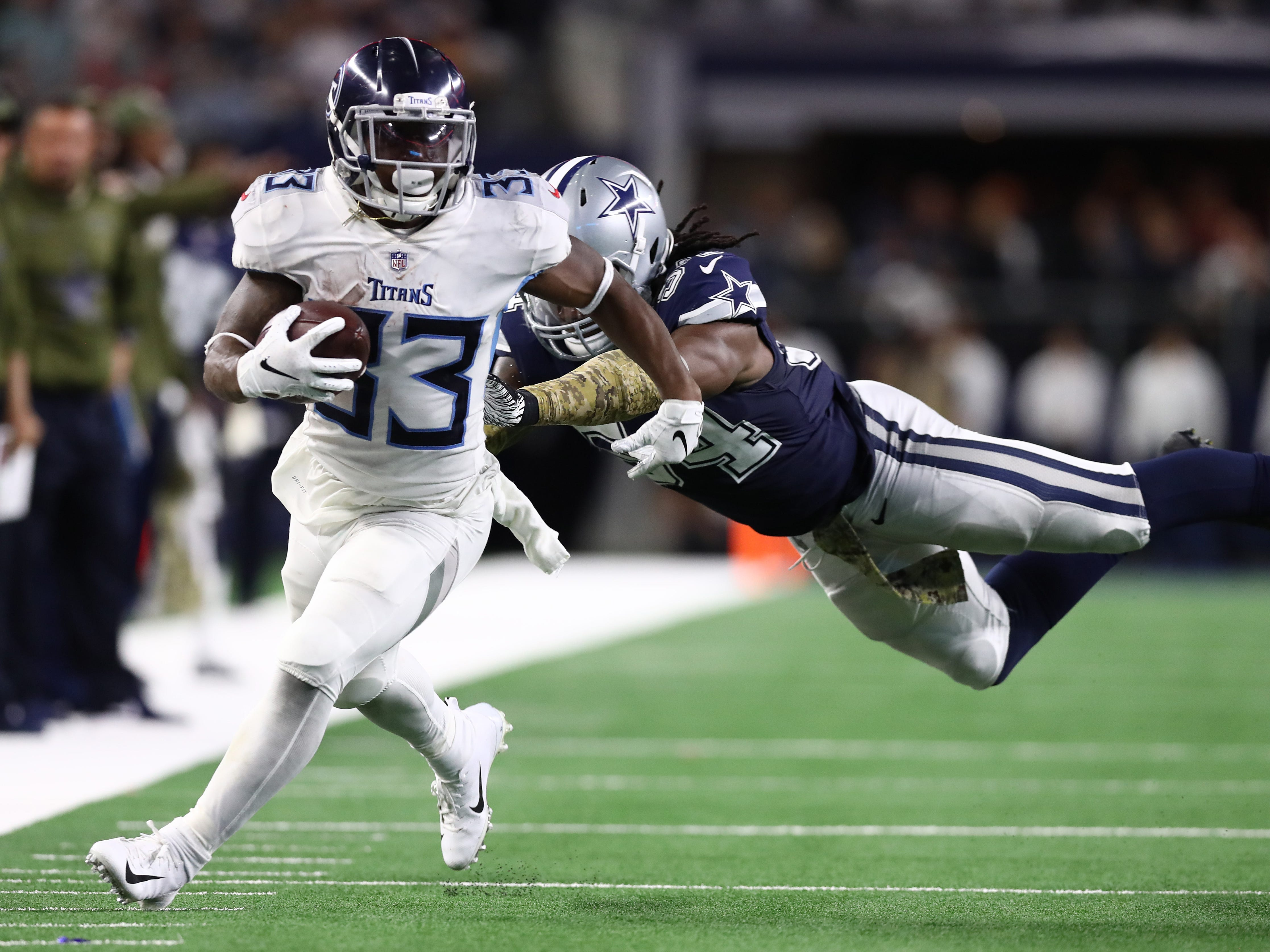 Tennessee Titans running back Dion Lewis (33) runs with the ball against Dallas Cowboys linebacker Jaylon Smith (54) in the fourth quarter at AT&T Stadium.