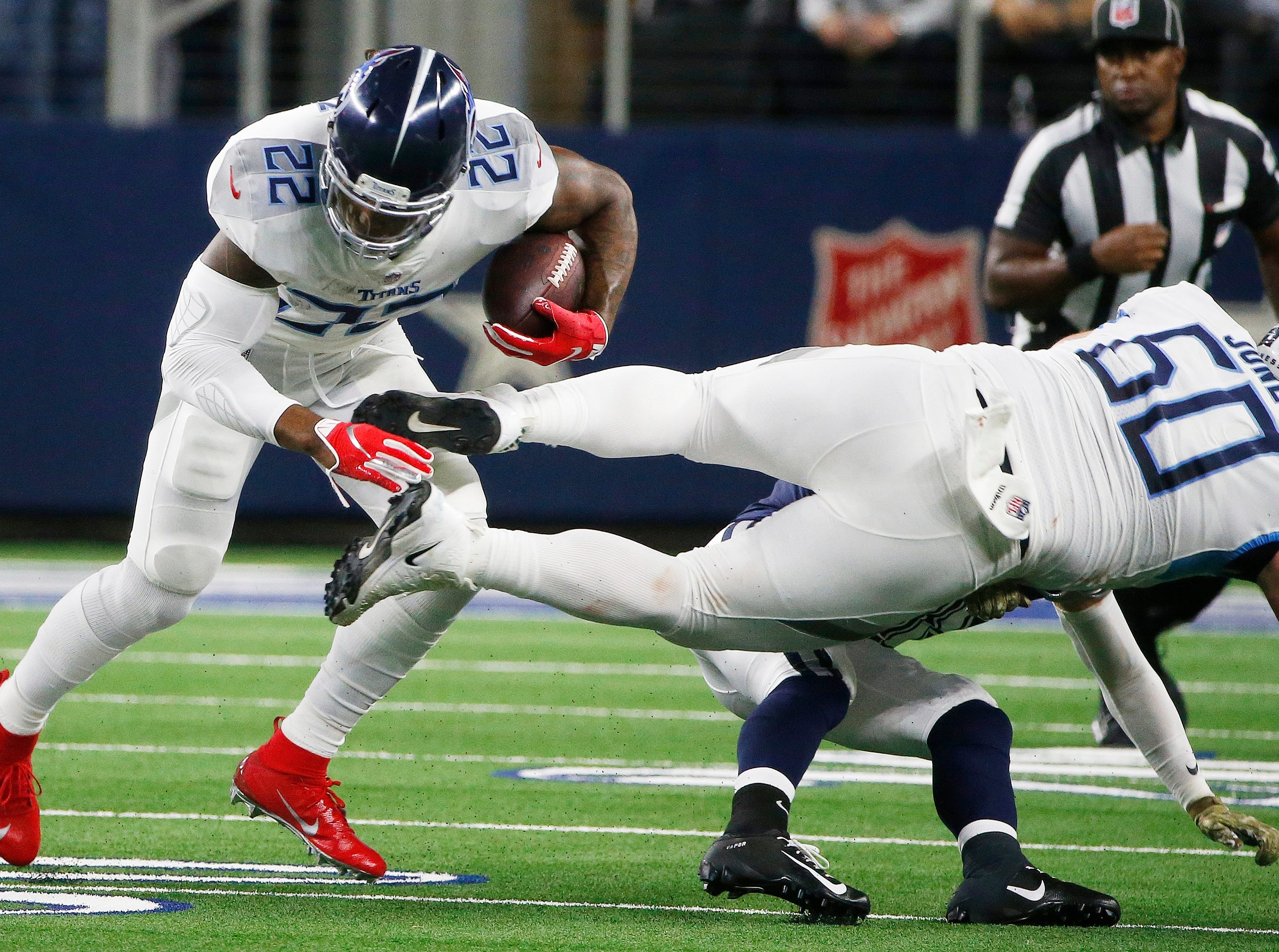Tennessee Titans running back Derrick Henry (22) runs as Tennessee Titans linebacker Nate Palmer (50) makes a block against the Dallas Cowboys during the first half of an NFL football game, Monday, Nov. 5, 2018, in Arlington, Texas.