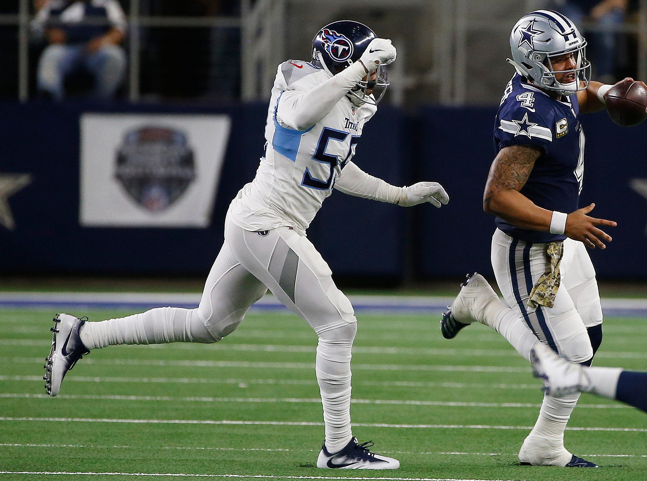 Dallas Cowboys quarterback Dak Prescott (4) is pursued by Tennessee Titans linebacker Jayon Brown (55) during the first half of an NFL football game, Monday, Nov. 5, 2018, in Arlington, Texas.