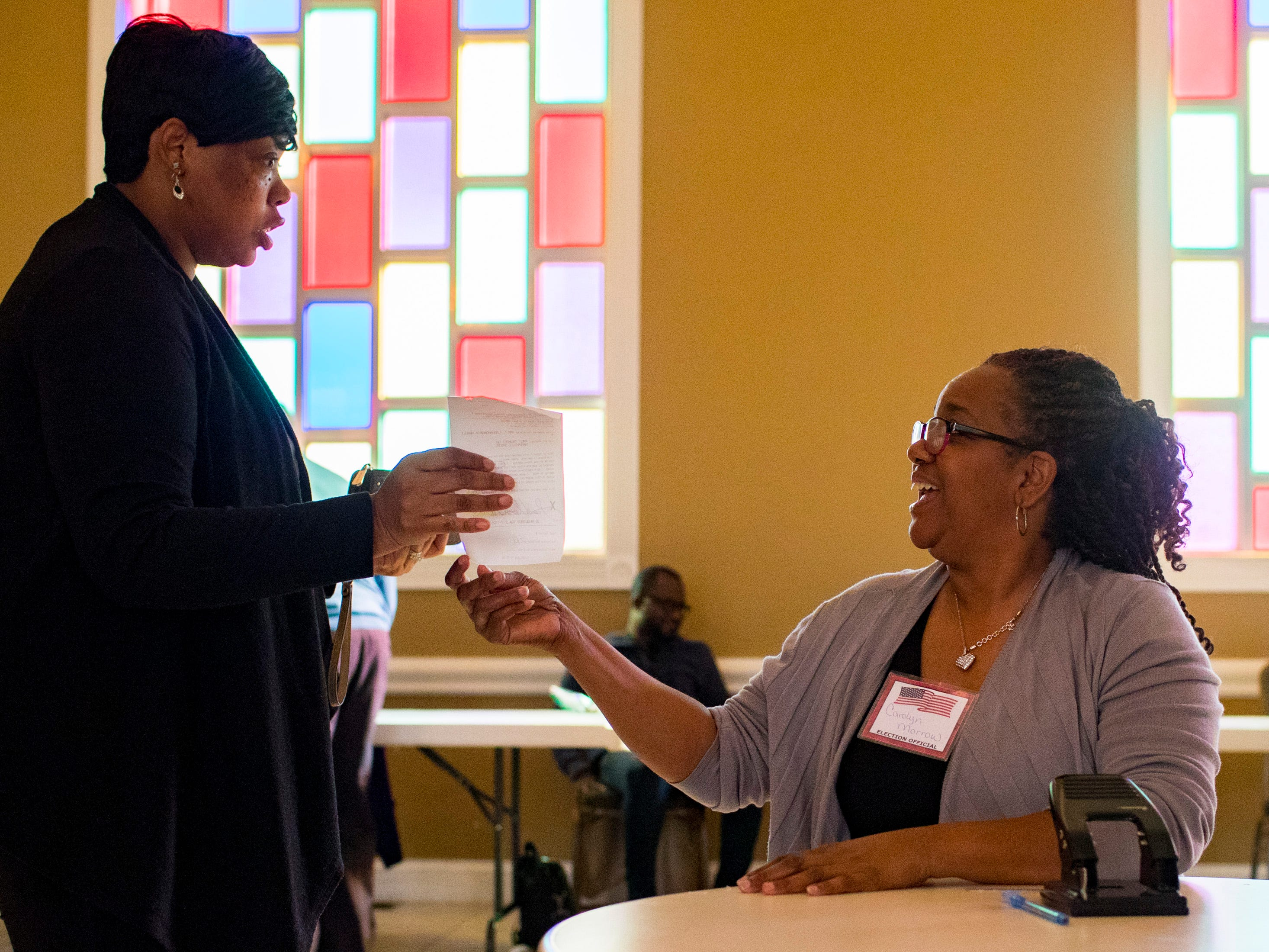 Election official Carolyn Morrow helps a voter at the Cathedral of Praise polling place in Nashville on Tuesday, Nov. 6, 2018.