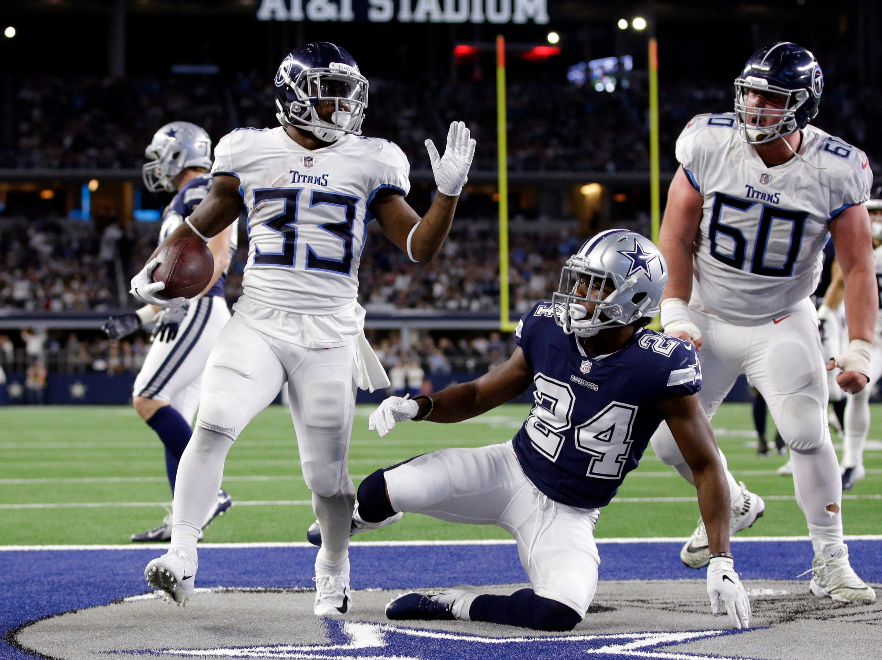Nov 5, 2018; Arlington, TX, USA; Tennessee Titans running back Dion Lewis (33) scores a touchdown against Dallas Cowboys cornerback Chidobe Awuzie (24) in the second quarter at AT&T Stadium.
