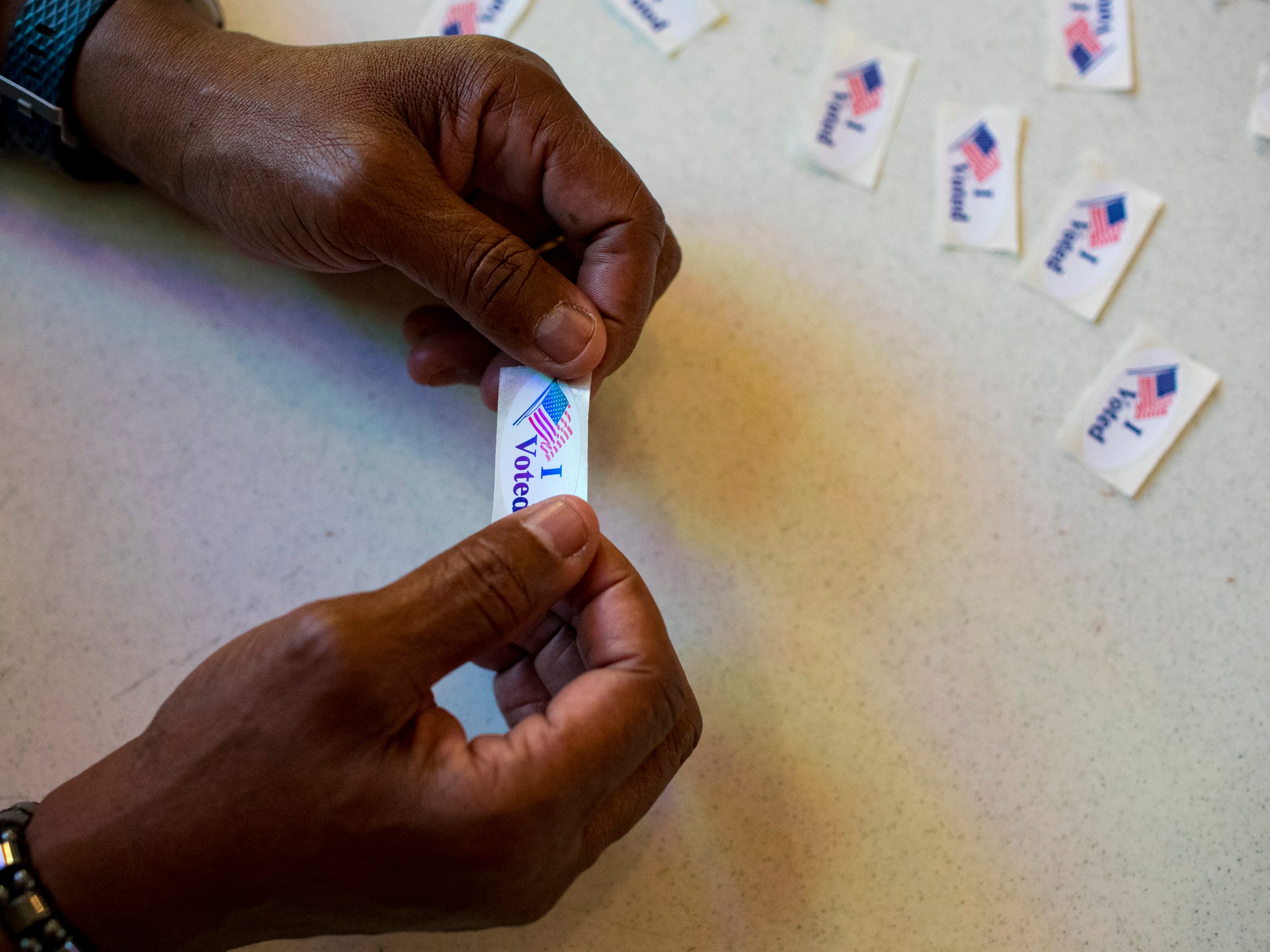 "Election official Thomas Shaw holds an ""I Voted"" sticker ready to hand to voters at the Cathedral of Praise in Nashville on Tuesday, Nov. 6, 2018."