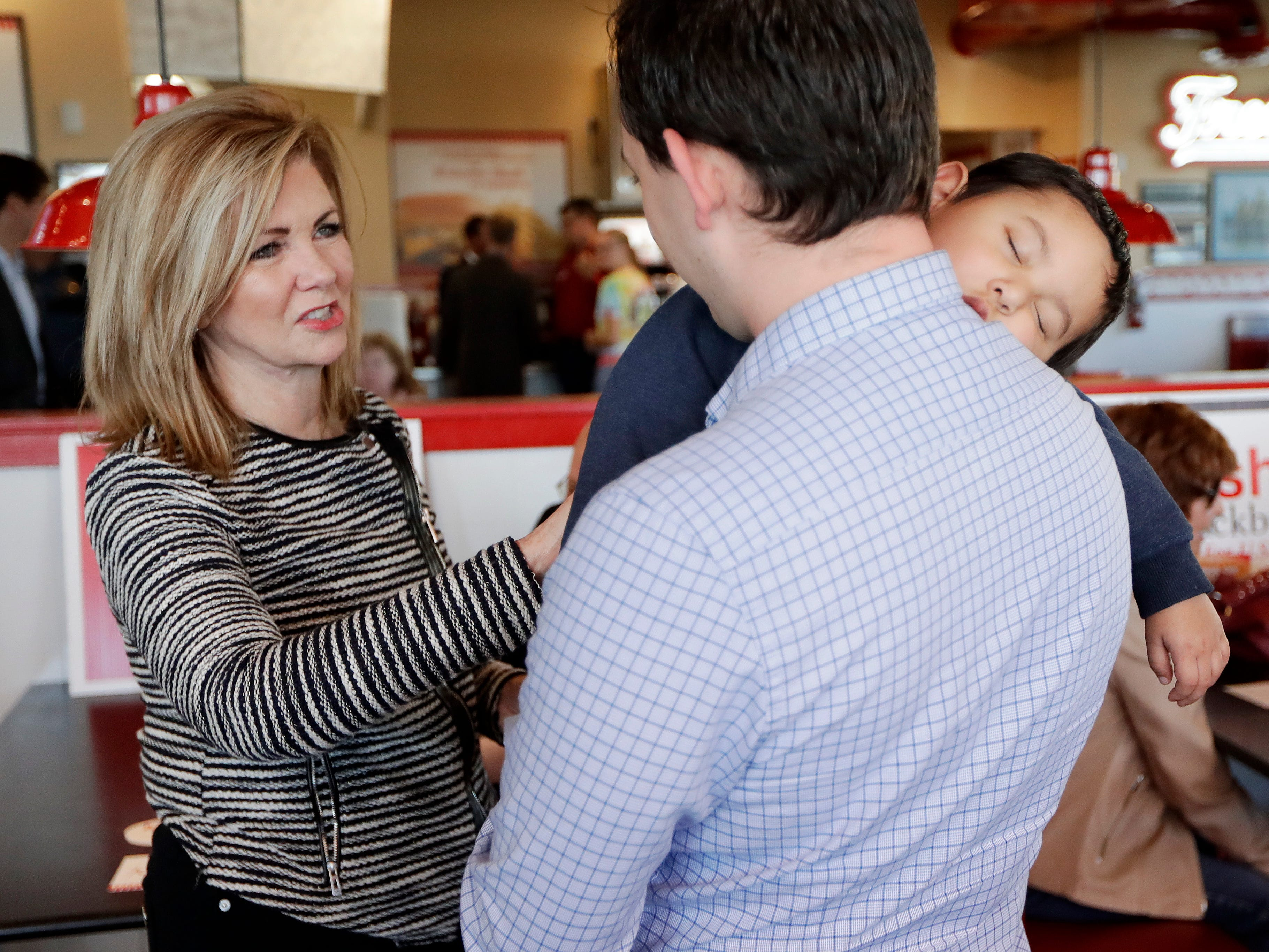 Rep. Marsha Blackburn, R-Tenn., campaigns at Freddy's Frozen Custard & Steakburgers and talks with David Frodin as his son, Noah, 2, naps Tuesday, Nov. 6, 2018, in Clarksville, Tenn. Blackburn is running against former Gov. Phil Bredesen for the U.S. Senate.