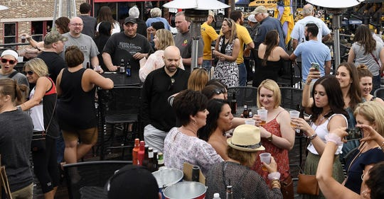 A crowd gathers on a rooftop bar at a Lower Broadway honky tonk in Nashville, Tenn.