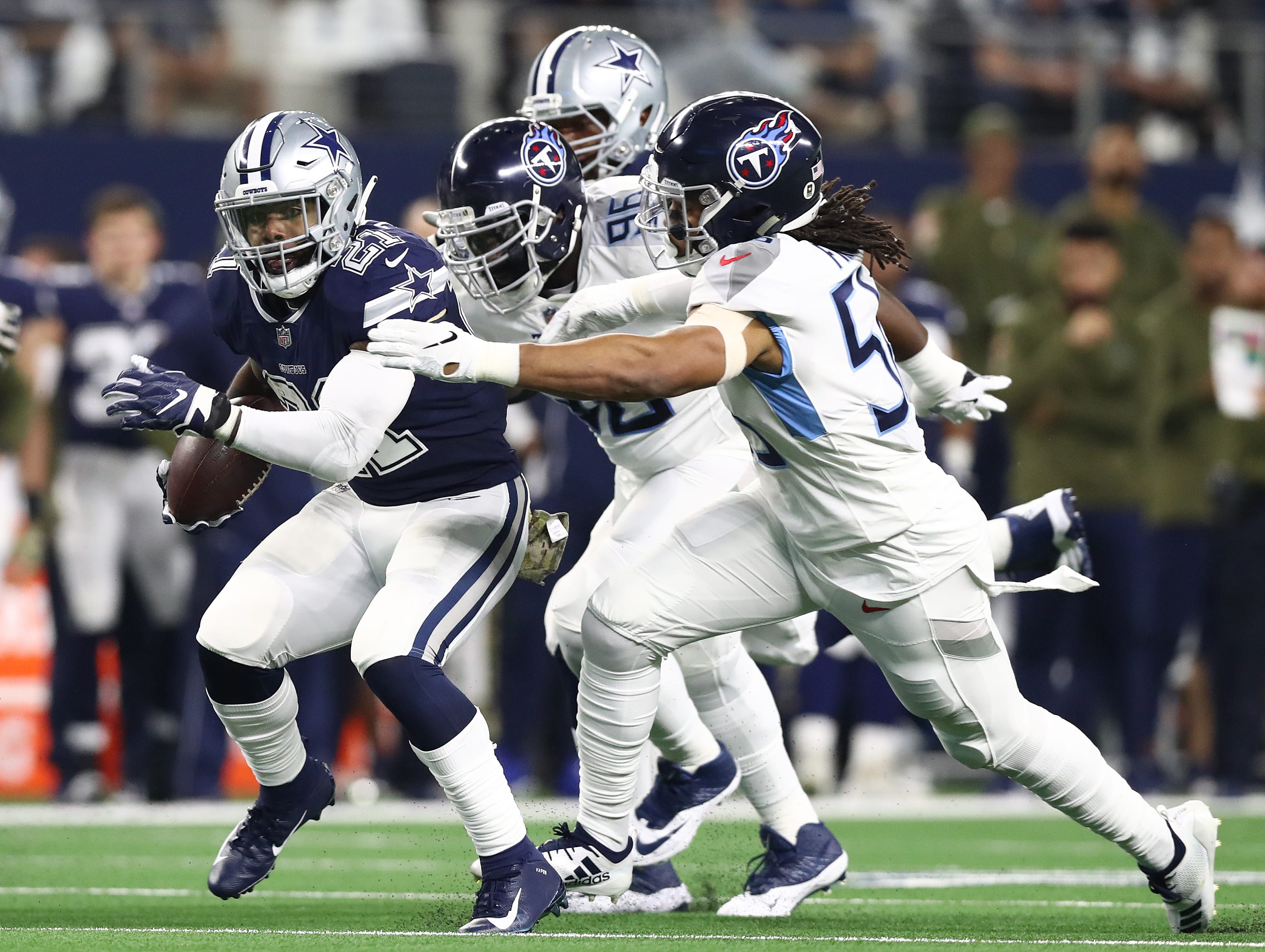 Nov 5, 2018; Arlington, TX, USA; Dallas Cowboys running back Ezekiel Elliott (21) runs with the ball against Tennessee Titans linebacker Sharif Finch (56) in the first quarter at AT&T Stadium.