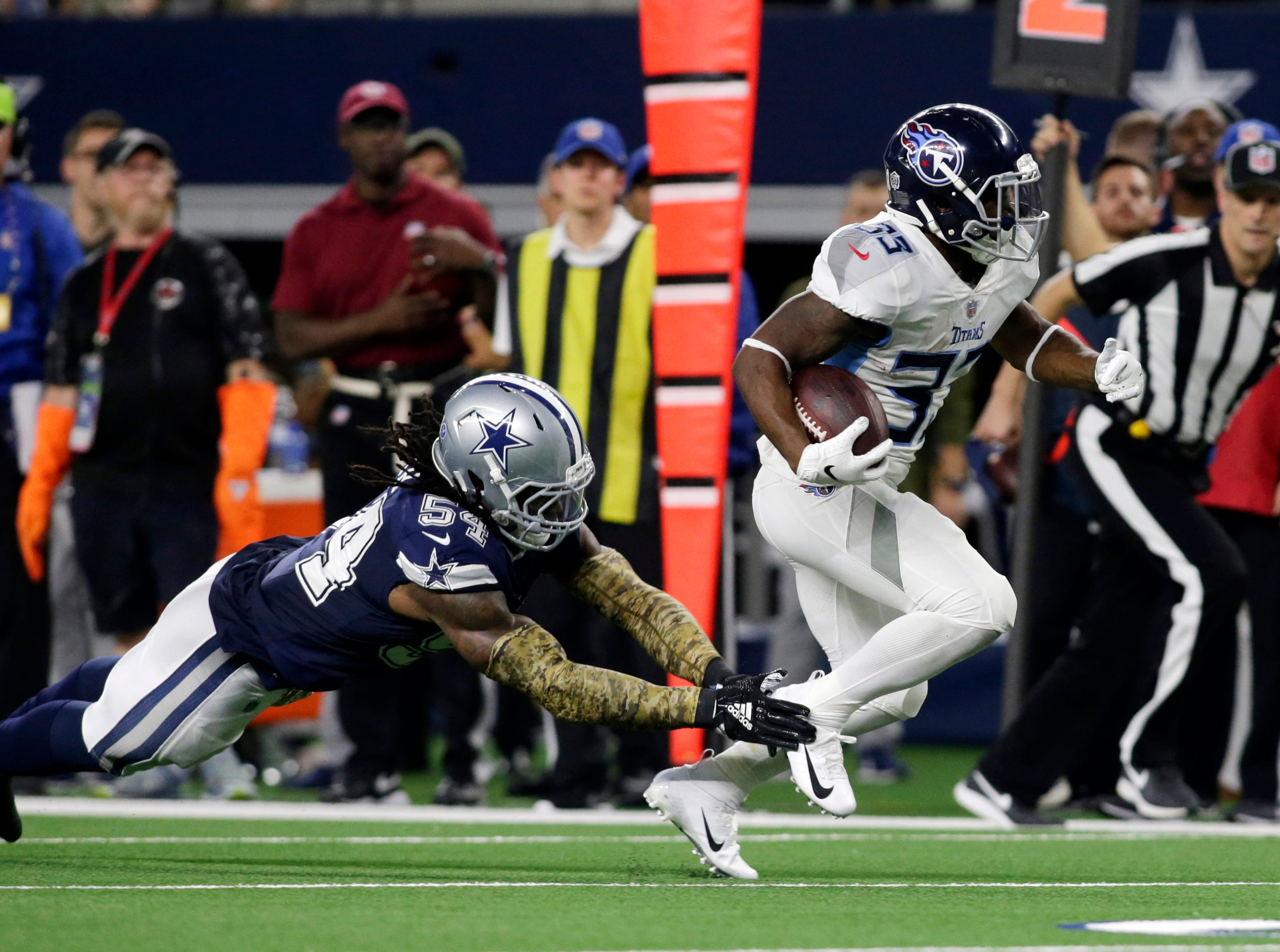 Nov 5, 2018; Arlington, TX, USA; Tennessee Titans running back Dion Lewis (33) runs against Dallas Cowboys middle linebacker Jaylon Smith (54) in the second quarter  at AT&T Stadium.