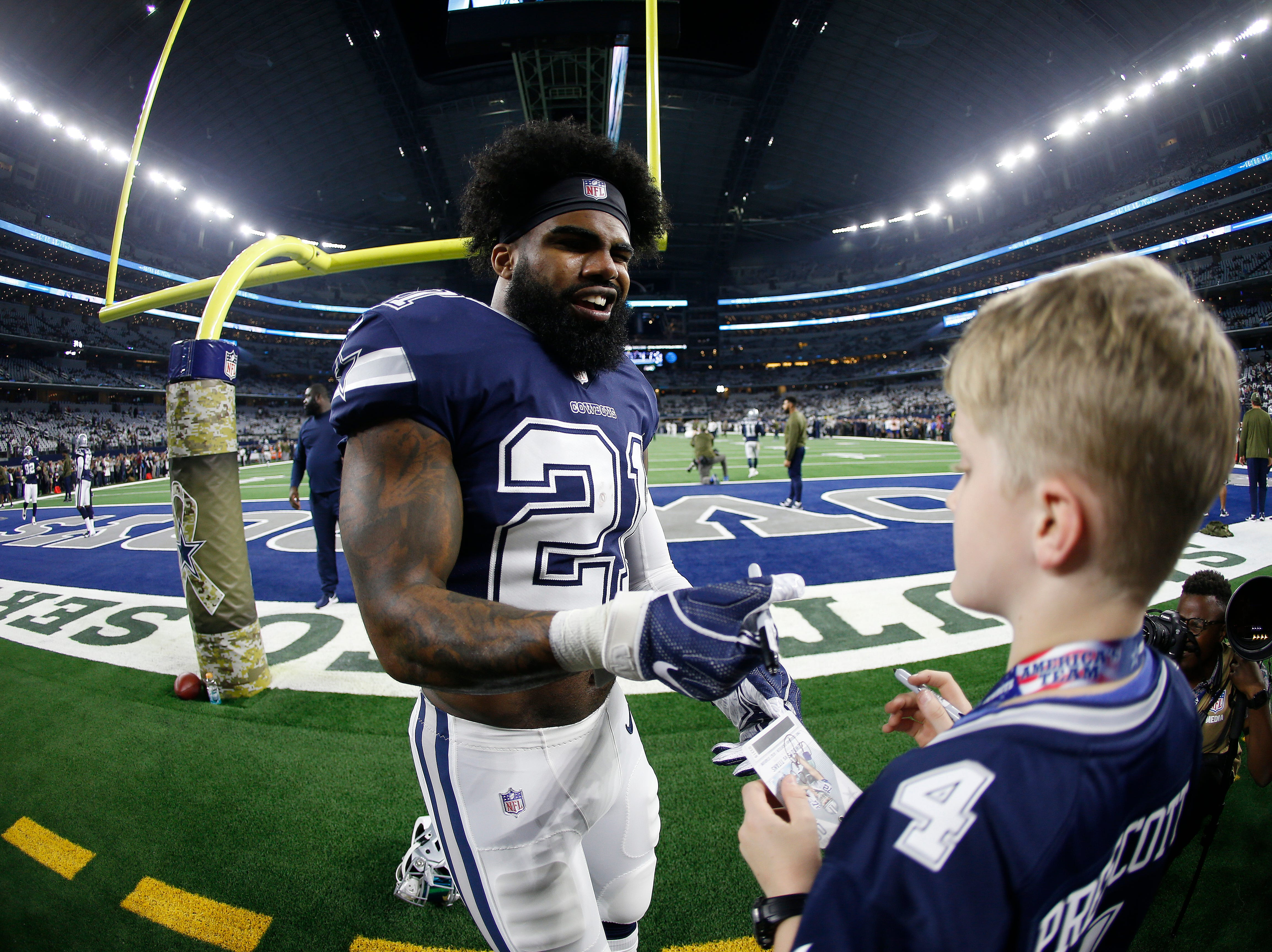 Dallas Cowboys running back Ezekiel Elliott (21) signs an autograph for a child before the first half of an NFL football game between the Dallas Cowboys and the Tennessee Titans, Monday, Nov. 5, 2018, in Arlington, Texas.