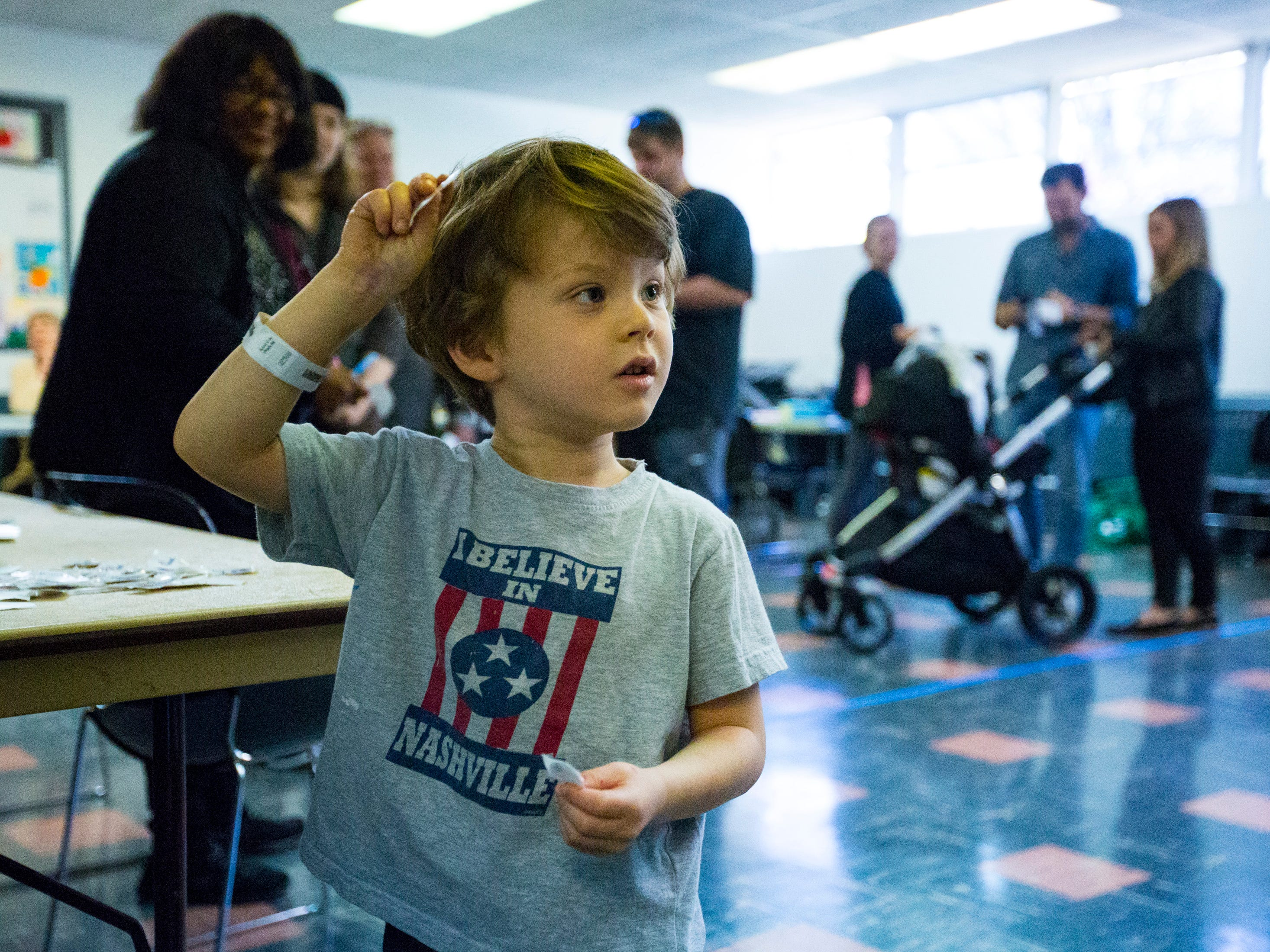 "Stone Scheideman, 5, picks up an ""I Voted"" sticker after helping his mom vote at the Shelby Park Community Center polling place in Nashville on Tuesday, Nov. 6, 2018."