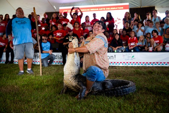 "Billy Walker wrestles an alligator during the 21st annual American Indian Arts Celebration on Friday, November 2, 2018, on the grounds of the Ah-Tah-Thi-Ki museum in the Big Cypress Seminole Indian Reservation. The Seminole people hunted alligators as a food source and for their hides, and the practice eventually became another source of income when tourists began paying to watch alligator wrestling. Walker's grandfather wrestled alligators, and he says he continues the tradition to hold on to his roots, ""I'm proud of who I am and I like to let people know that we're still here, we'll always be here, part of Florida."""
