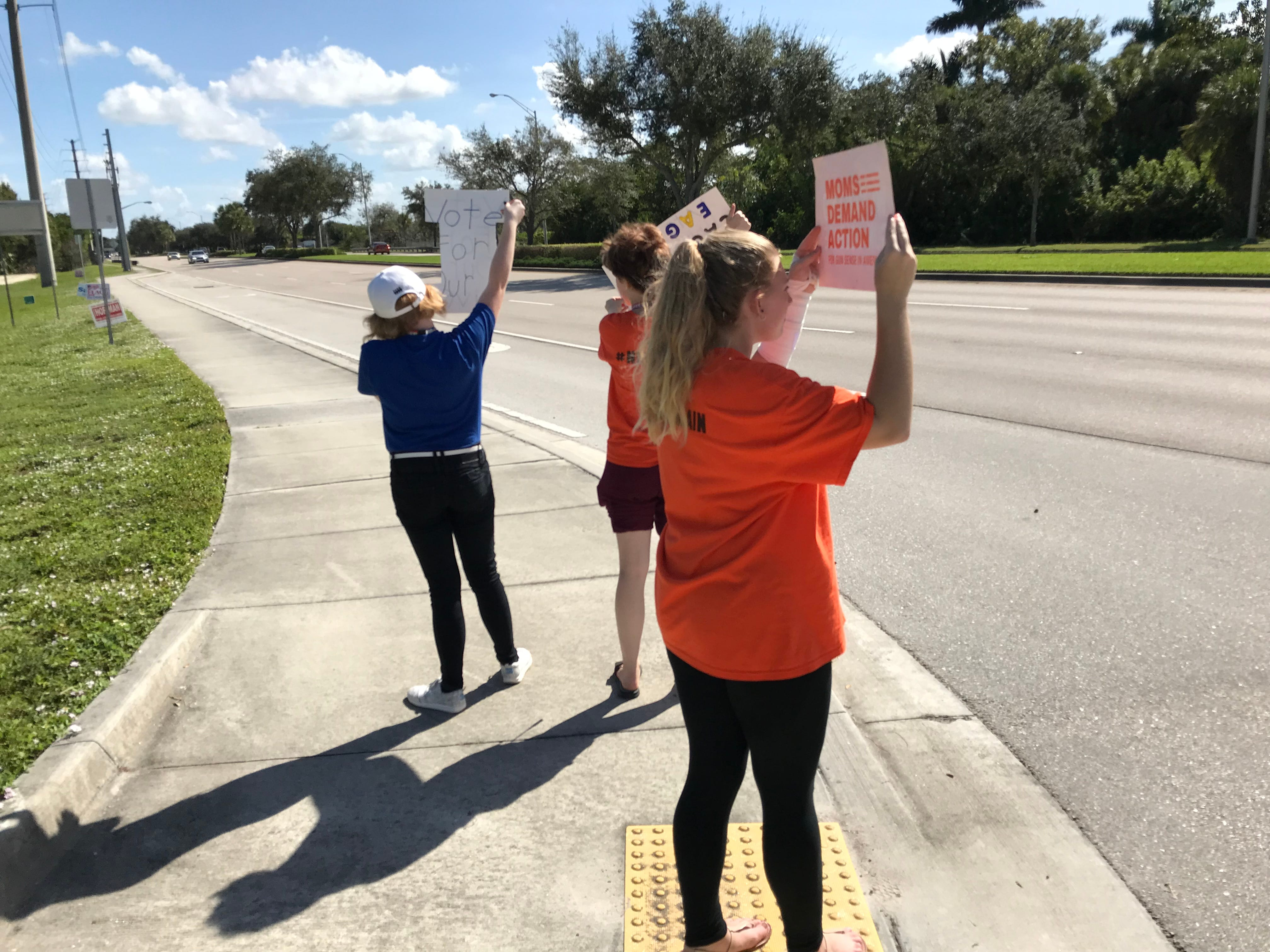 Students from Naples High School hold up signs during an Election Day student walkout at Freedom Park in Naples on Tuesday, Nov. 6, 2018.